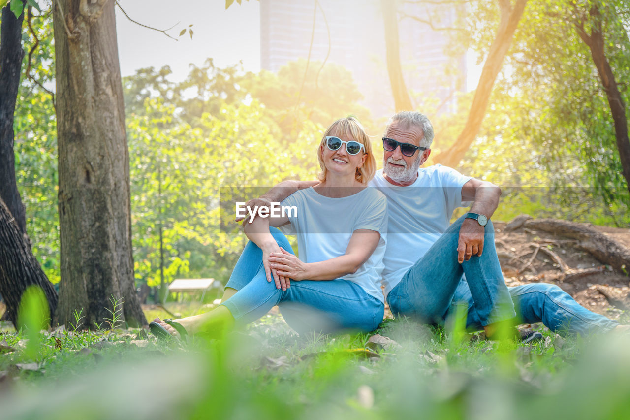 togetherness, plant, casual clothing, two people, lifestyles, leisure activity, men, males, tree, day, women, bonding, real people, adult, nature, land, smiling, sitting, front view, child, outdoors, mature men, son