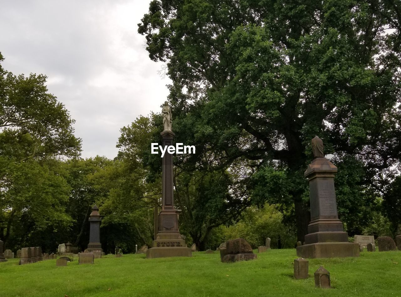 tree, cemetery, tombstone, memorial, grass, day, gravestone, graveyard, sky, history, outdoors, cloud - sky, no people, growth, nature