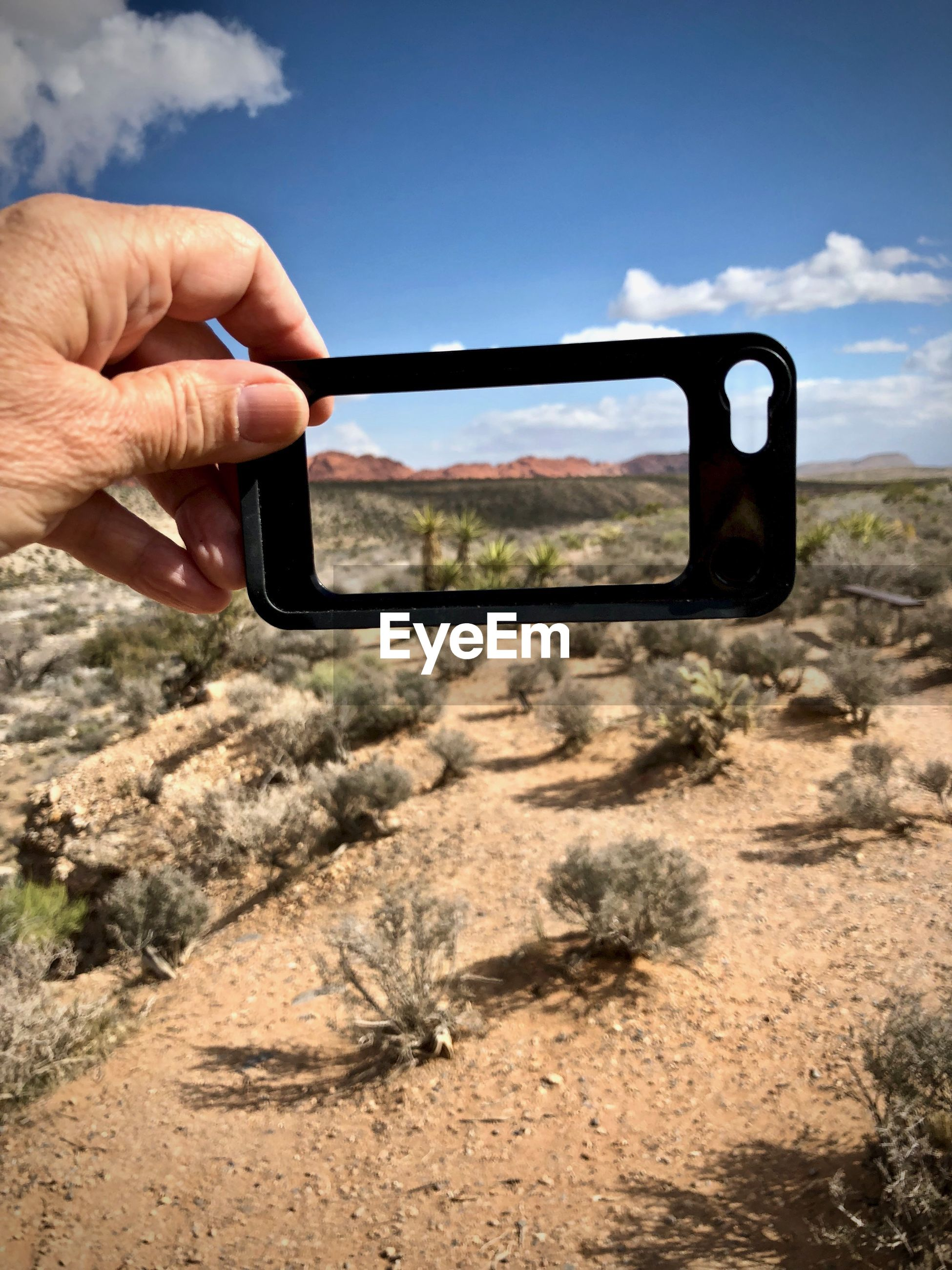 Close-up of hand holding phone cover in desert against sky