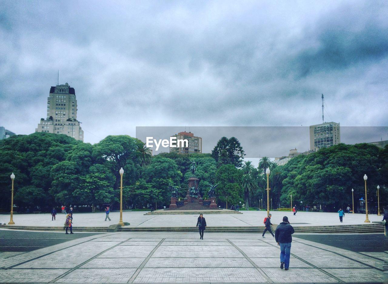 People walking in city park against cloudy sky