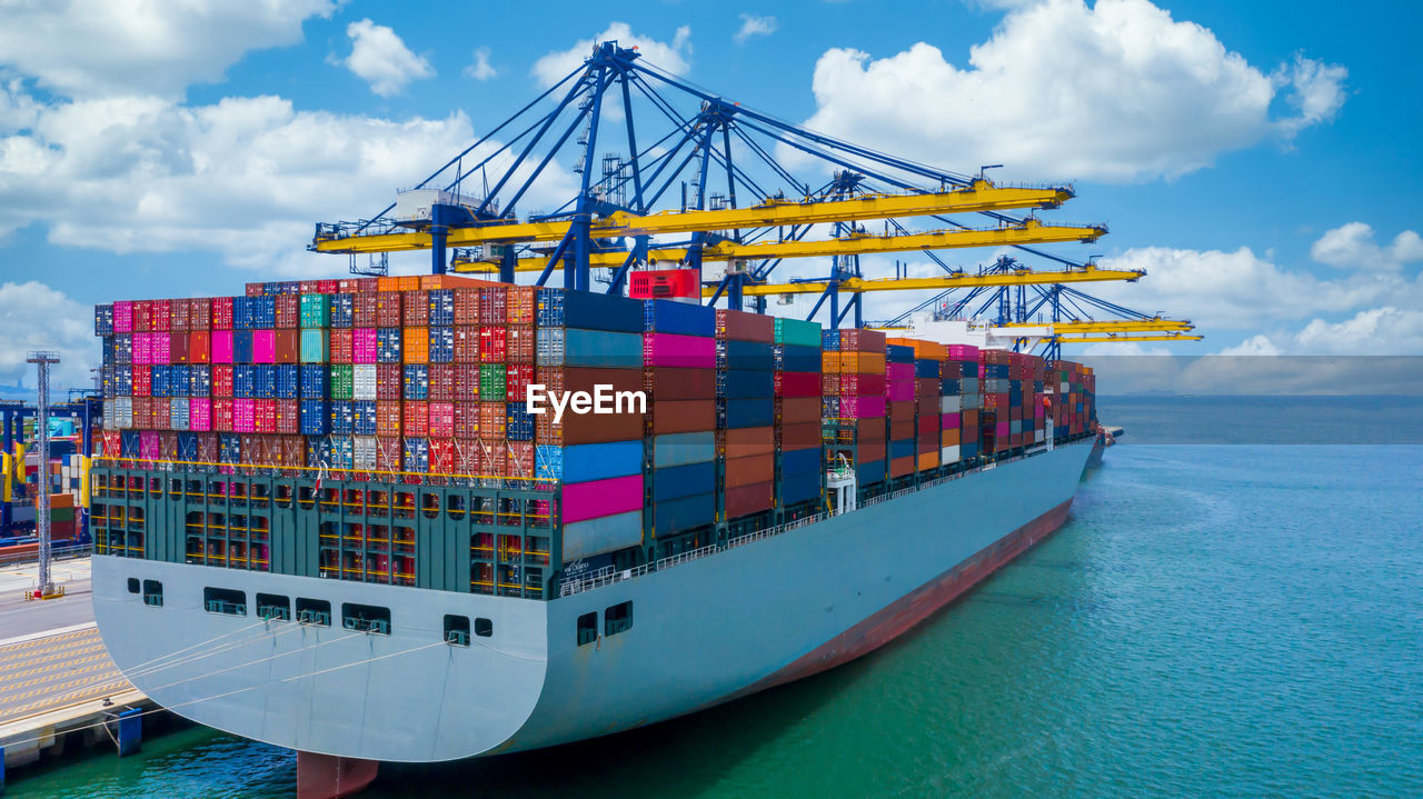 Container ship unloading crane ship seaport, global business logistic import export freight shipping