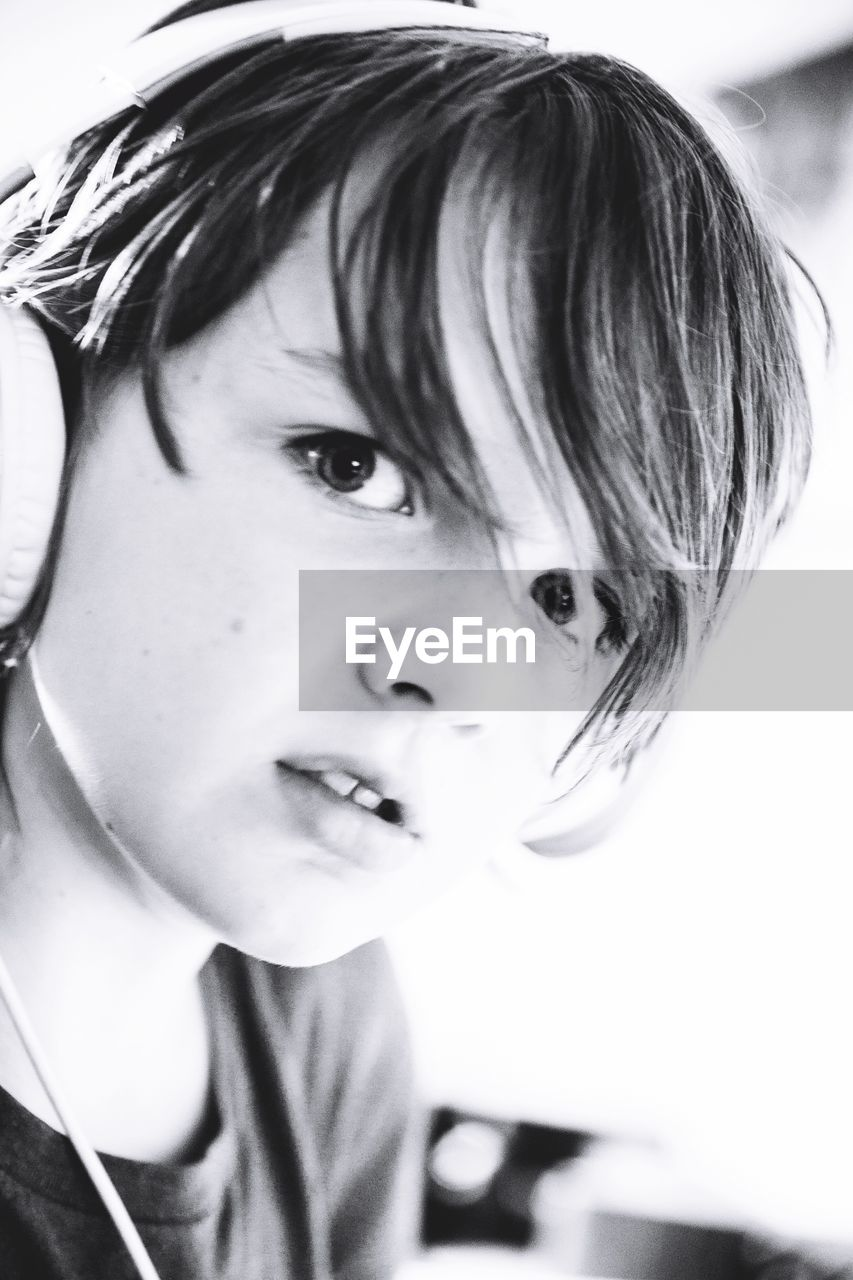 Close-Up Portrait Of Boy Listening To Music