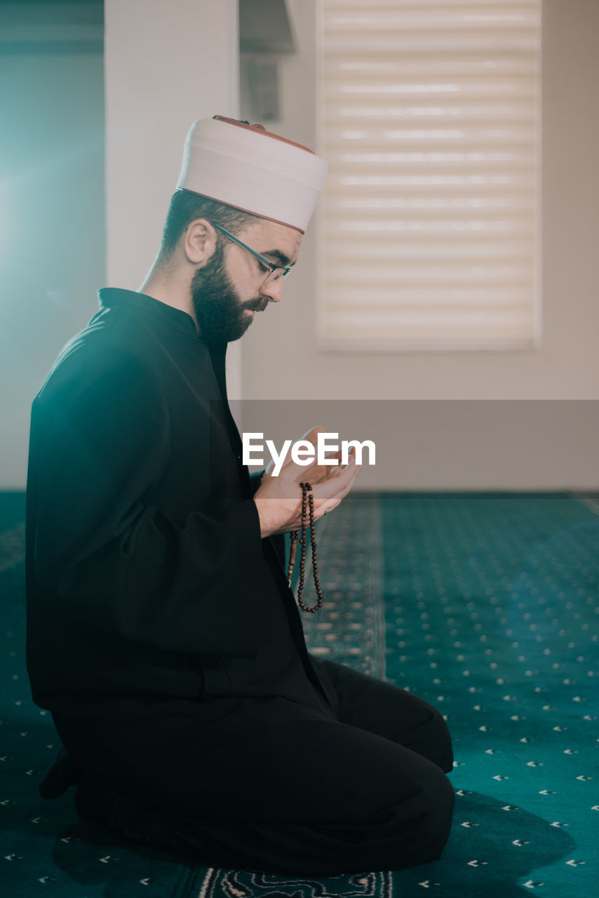 Side view of man praying while sitting in mosque
