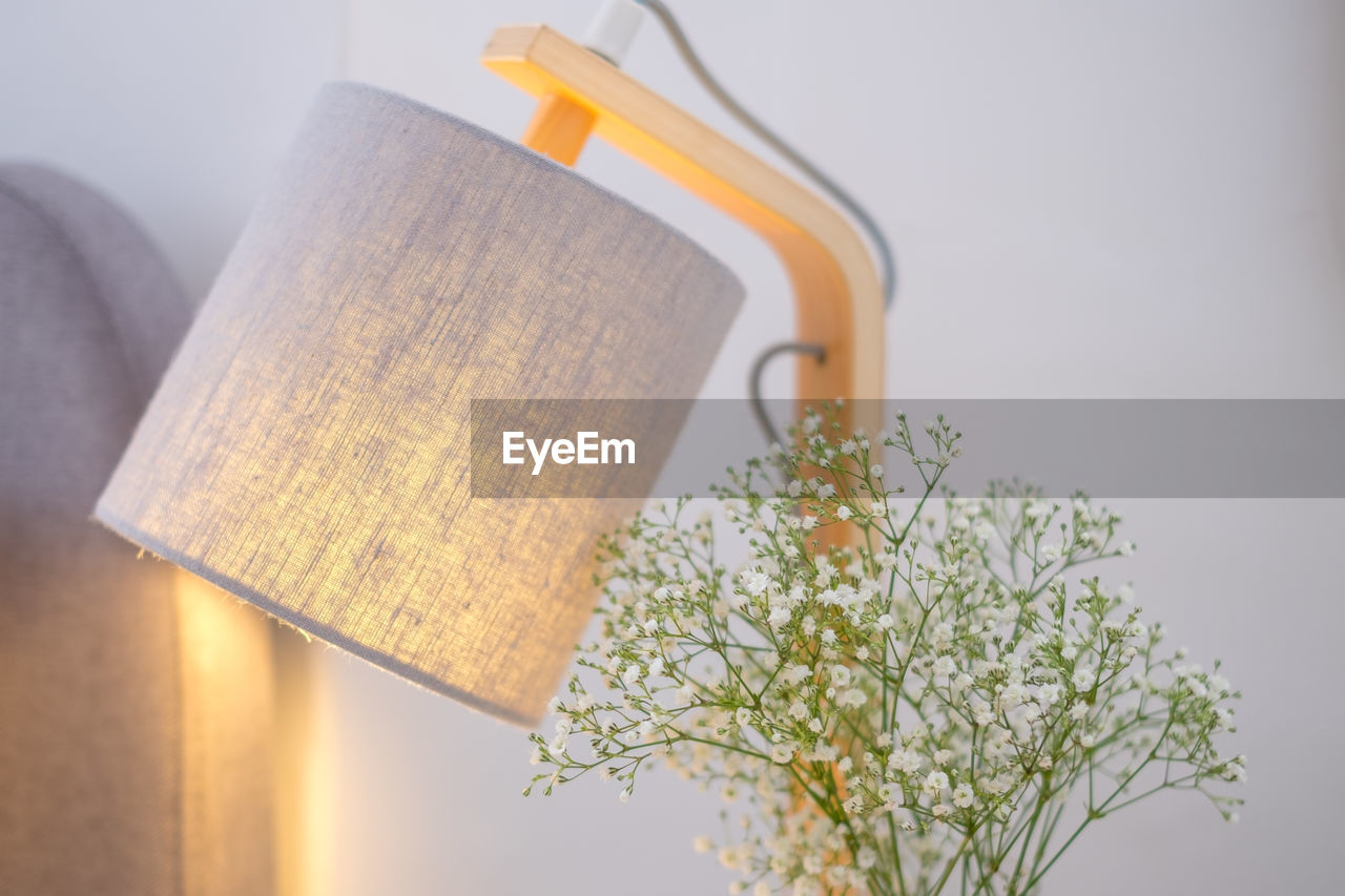 Close-up of illuminated electric lamp against wall at home