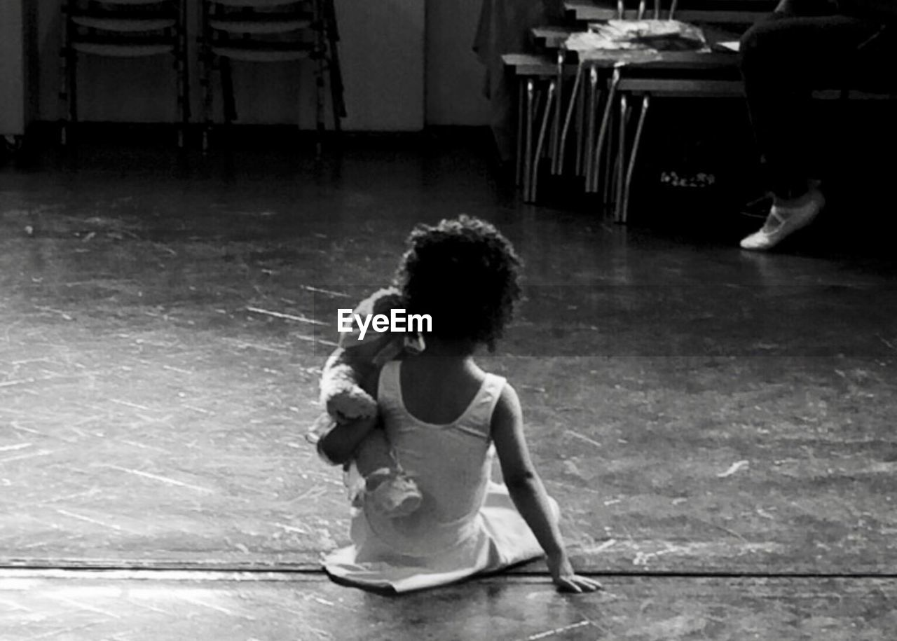 Rear View Of Girl With Teddy Bear Sitting On Floor At Ballet Studio