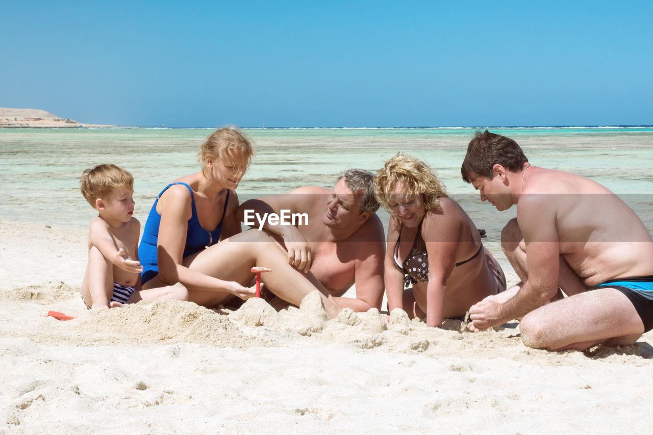Happy Family Enjoying At Beach On Sunny Day