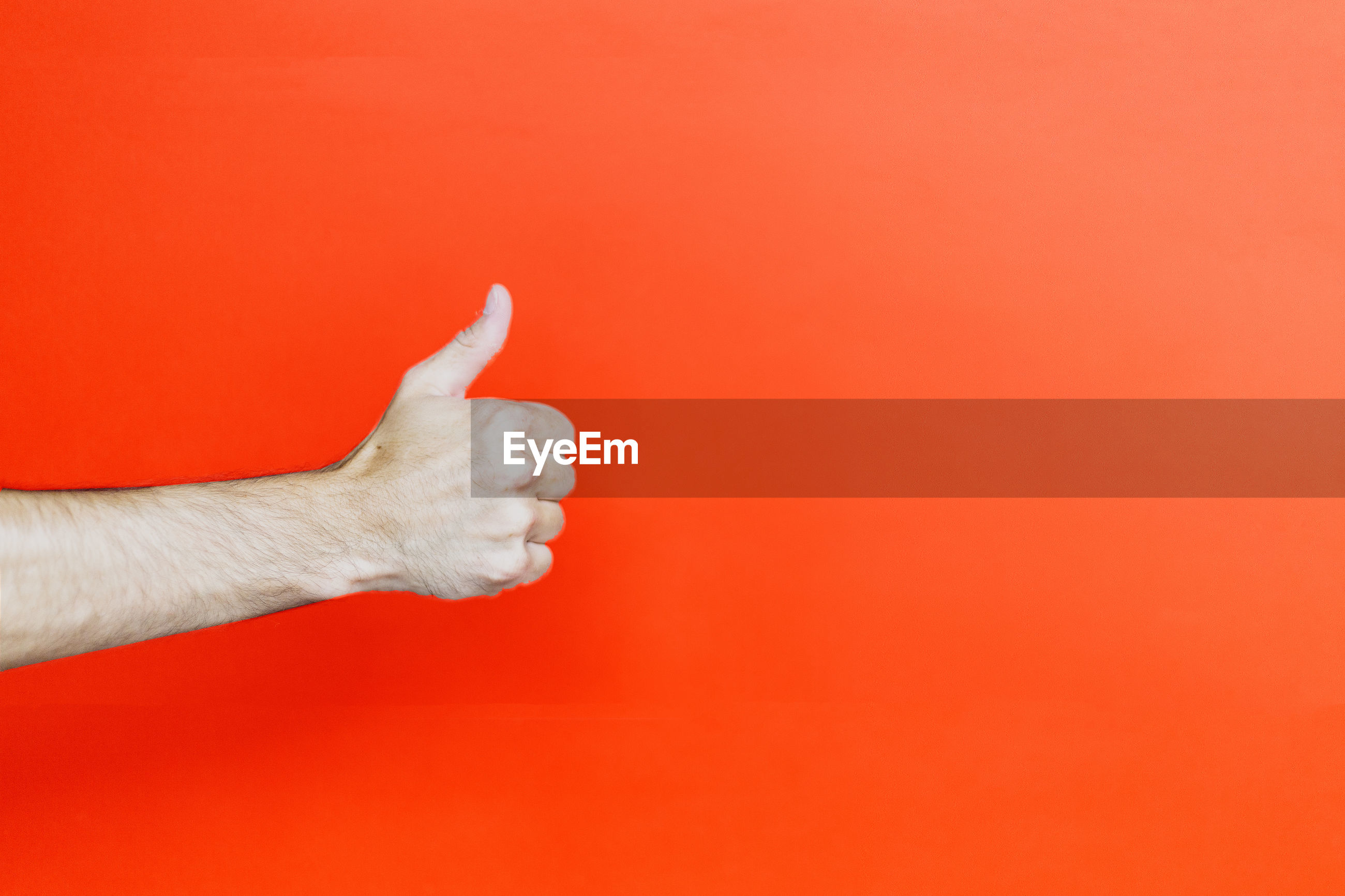 Close-up of hand showing thumbs up against orange background