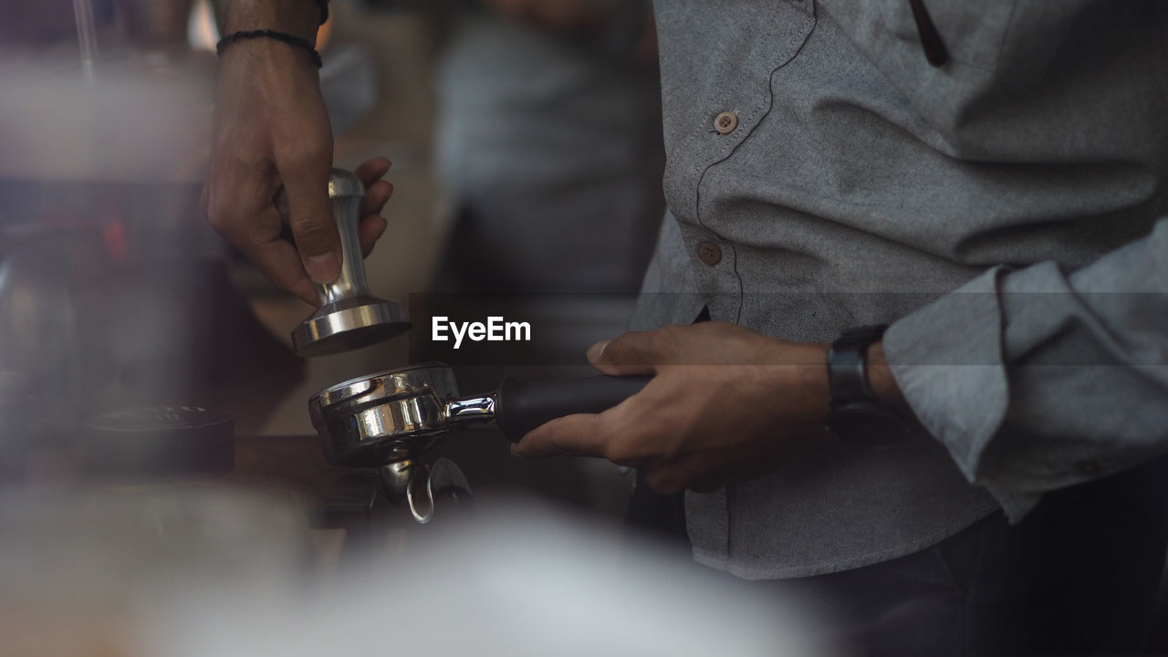 Close up of a male barista hand preparing to make a cup of coffee. selected focus.