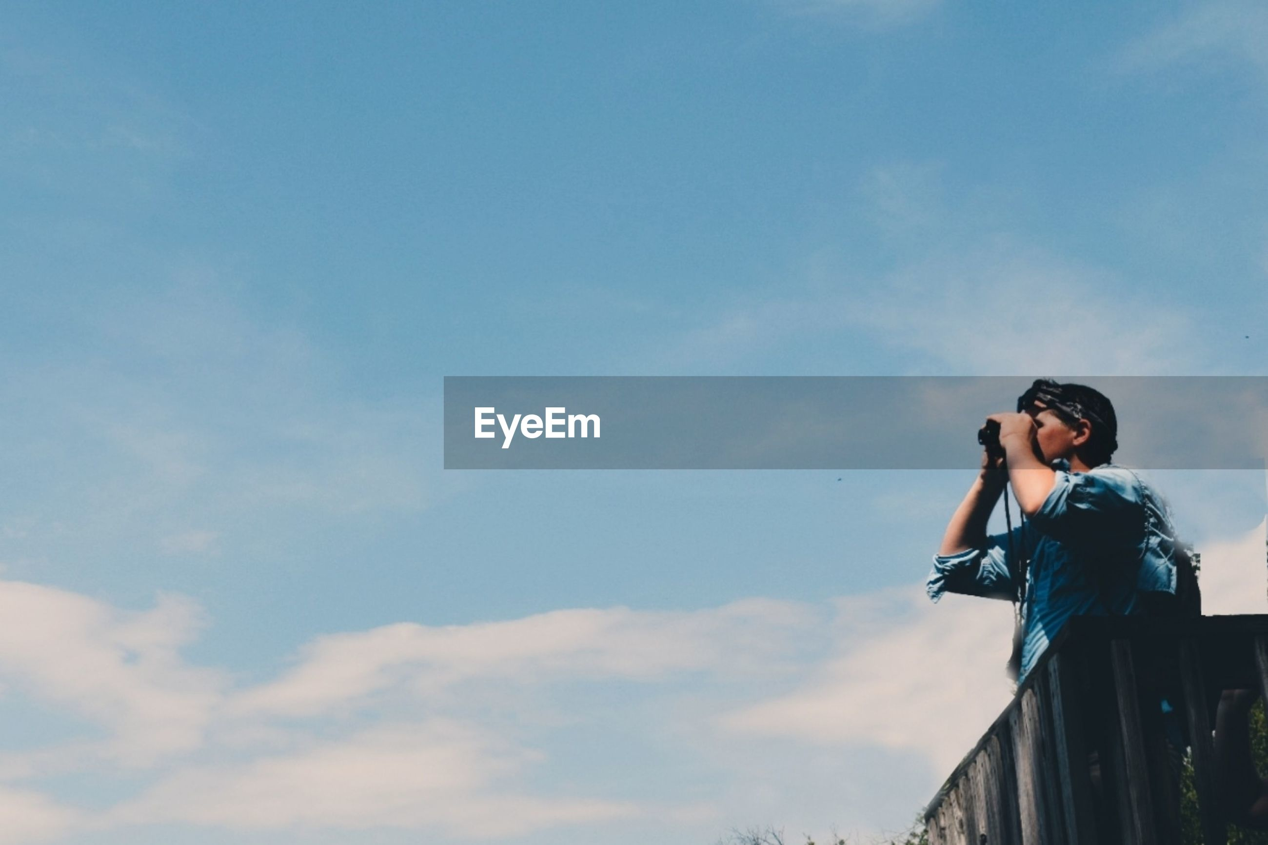 Low angle view of man looking through binoculars while standing against cloudy sky