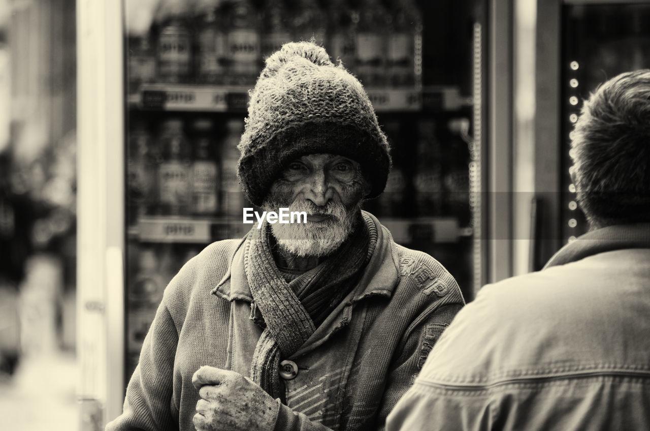 PORTRAIT OF MAN WEARING HAT IN CITY