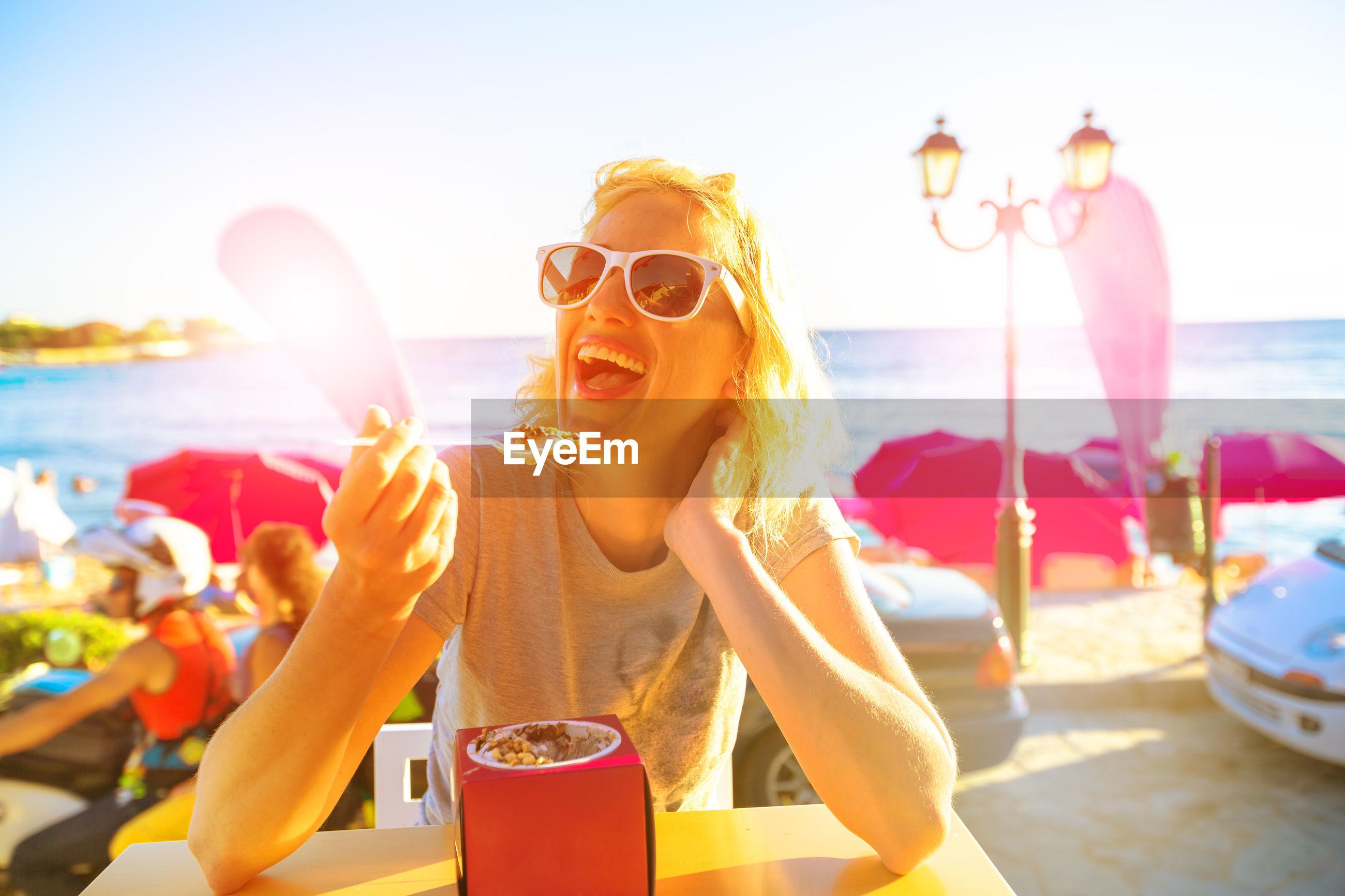 Portrait of cheerful woman having food at beach restaurant against sky