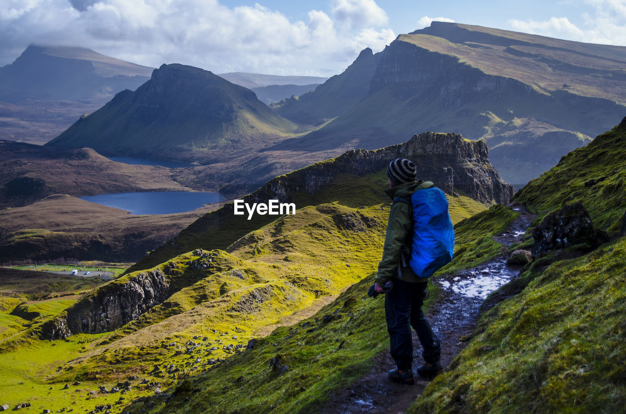 Side View Of Man With Backpack Standing On Mountain Against Sky