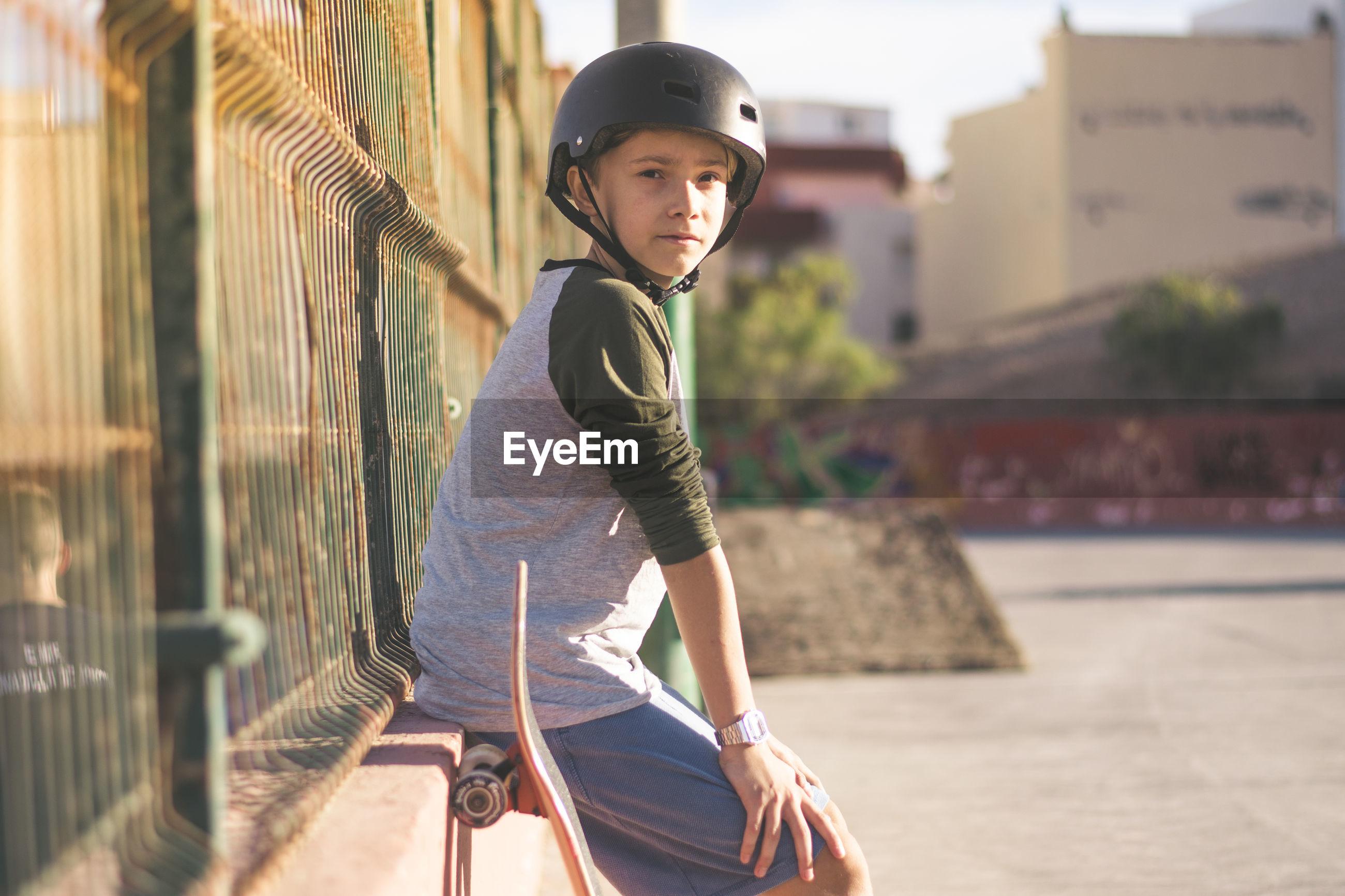 Portrait of boy wearing skateboard helmet by fence