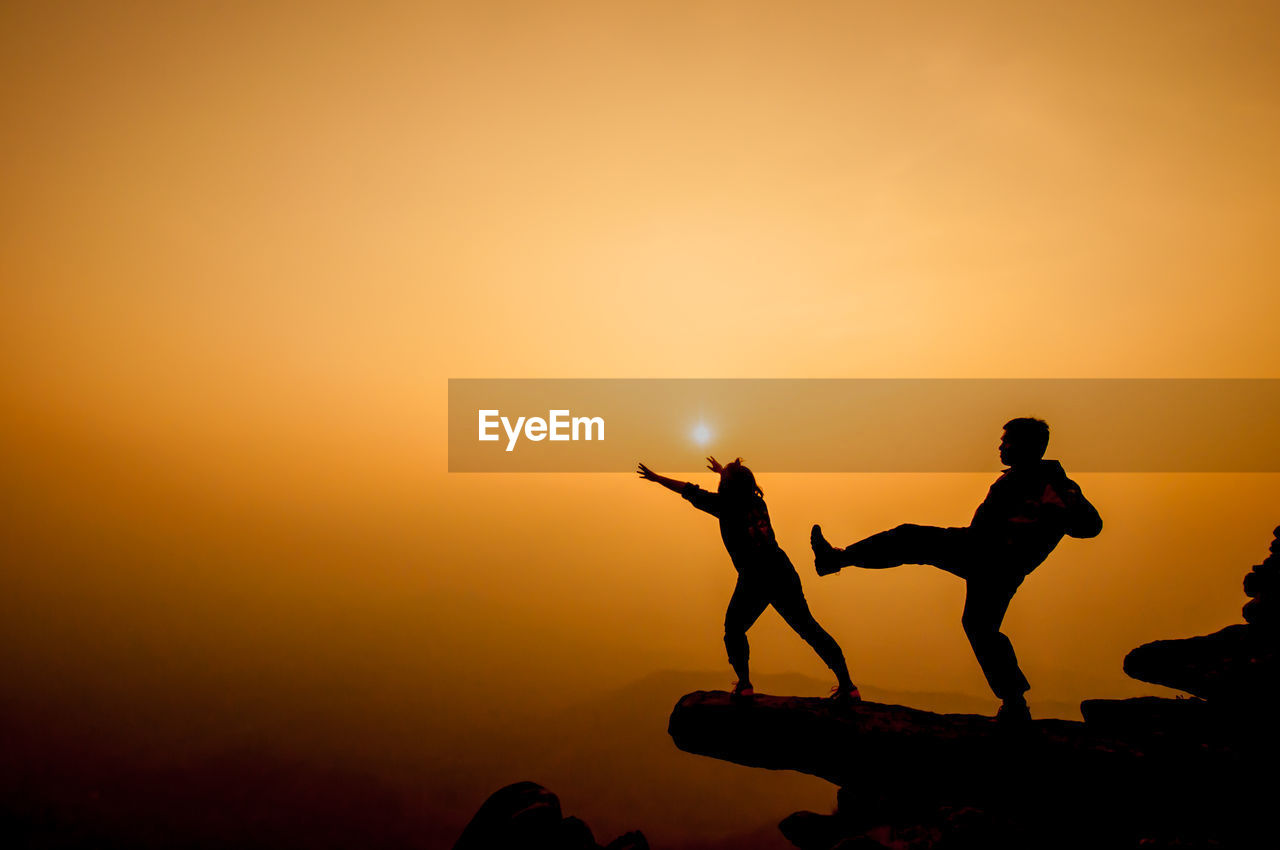 Silhouette man kicking woman from cliff against sky during sunset