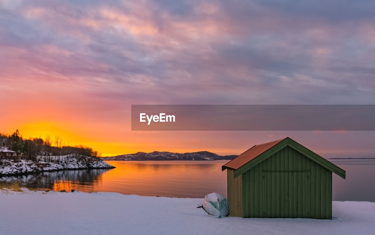 sunset, sky, orange color, nature, built structure, beauty in nature, tranquility, cloud - sky, tranquil scene, outdoors, scenics, water, no people, architecture, building exterior, winter, sea, snow, day
