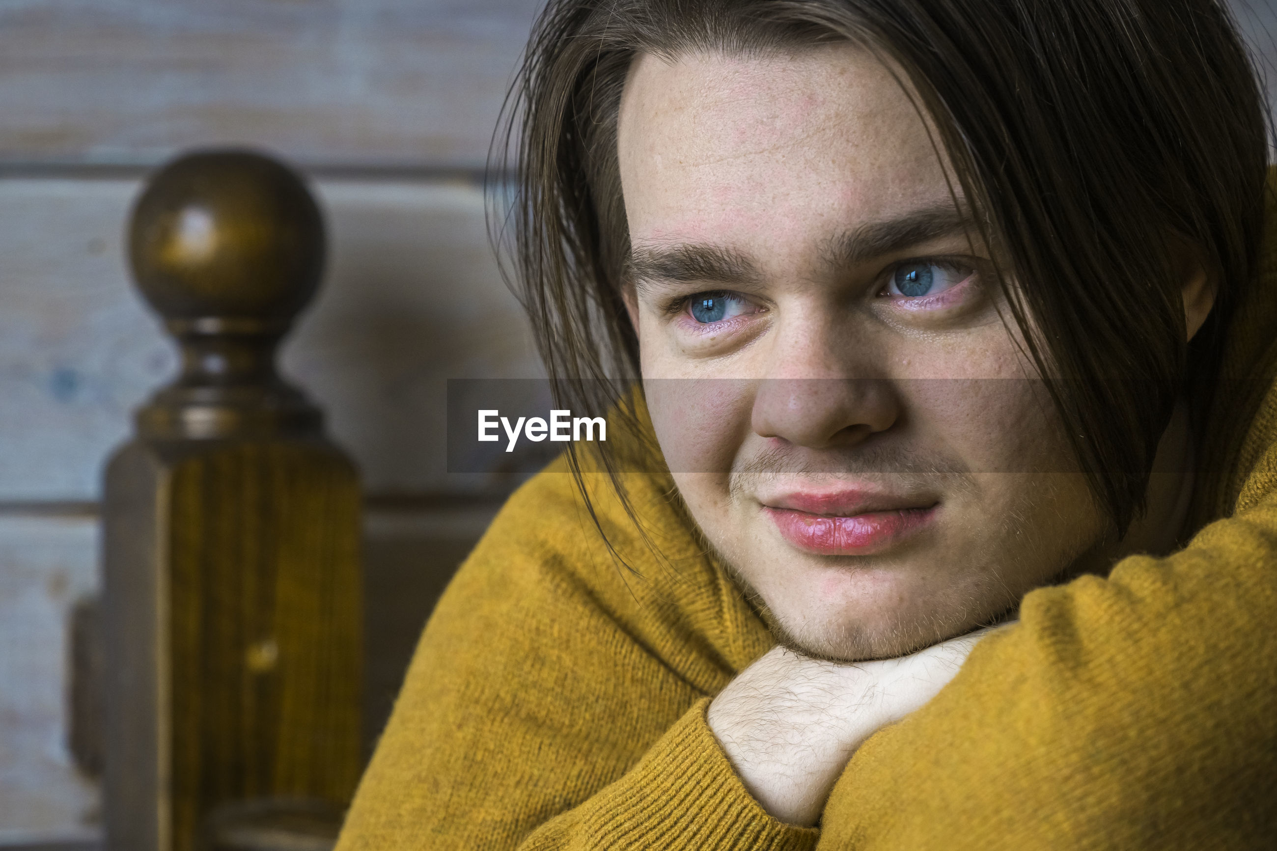Close-up of smiling young man wearing sweater looking away while leaning on wooden railing at home