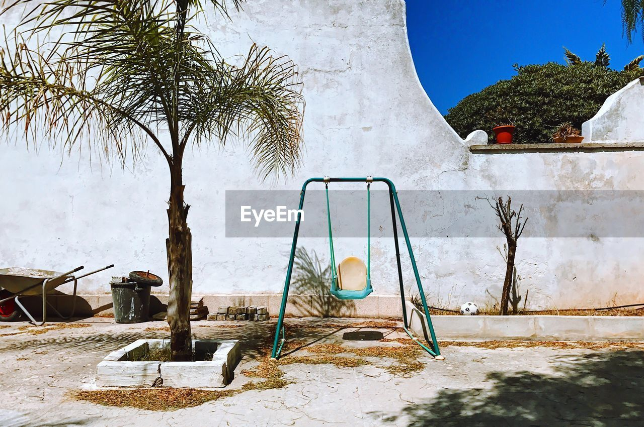tree, plant, nature, architecture, day, no people, palm tree, built structure, tropical climate, snow, growth, cold temperature, sky, outdoors, building exterior, building, winter, sunlight, playground