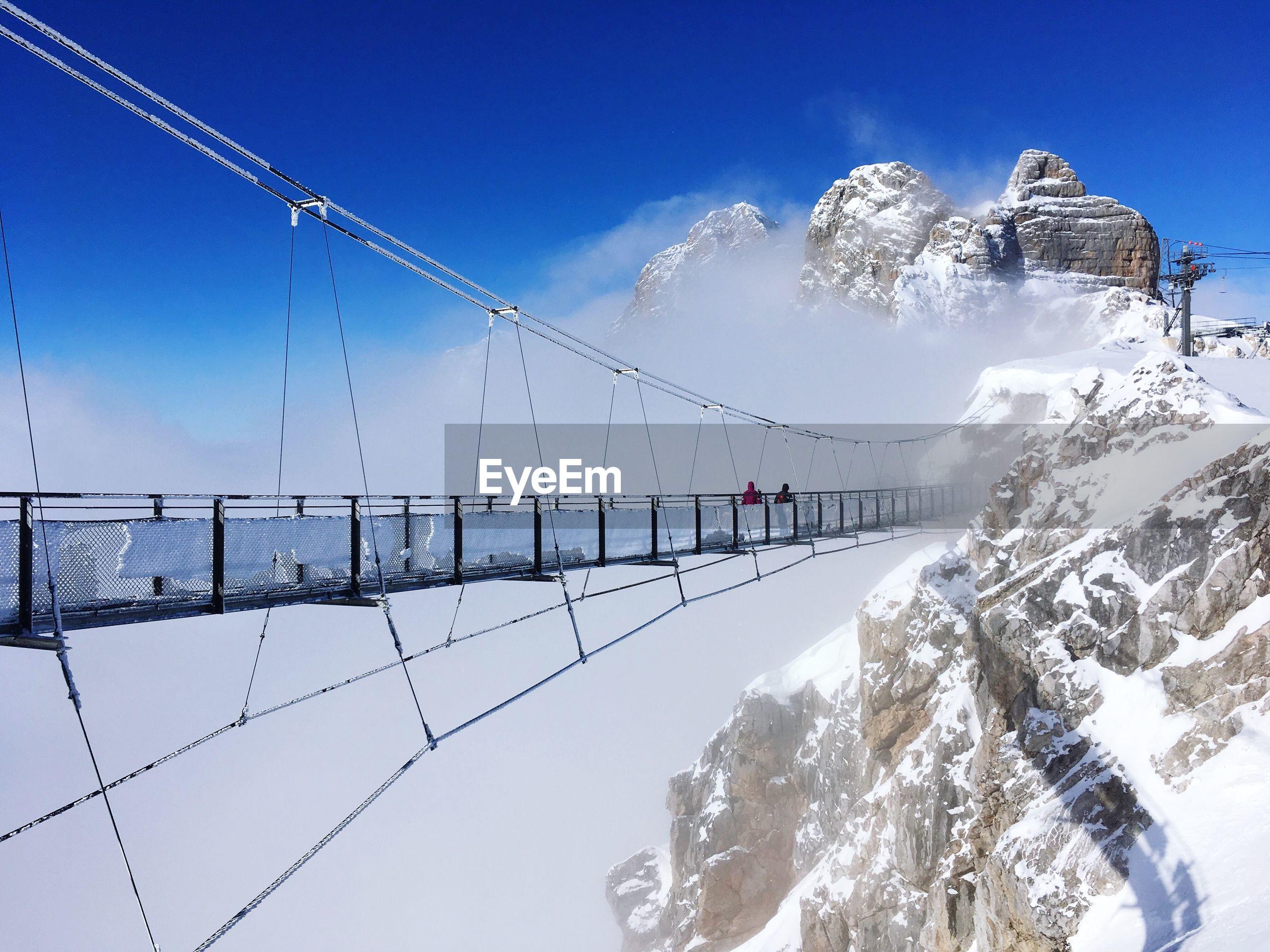 SNOW COVERED BRIDGE AGAINST SKY