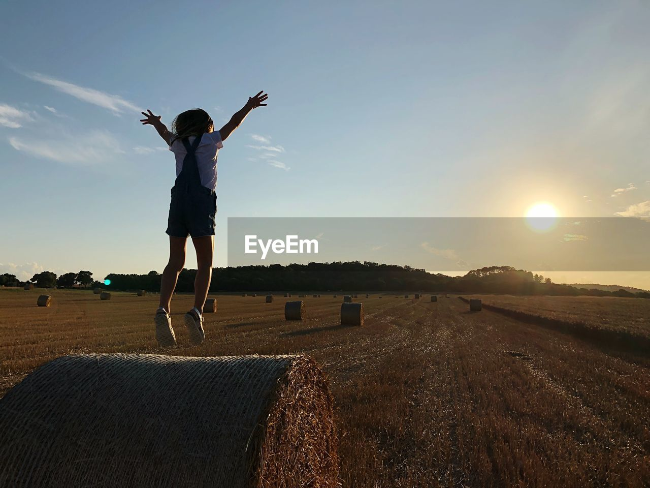 Rear view of girl jumping on landscape against sky during sunset