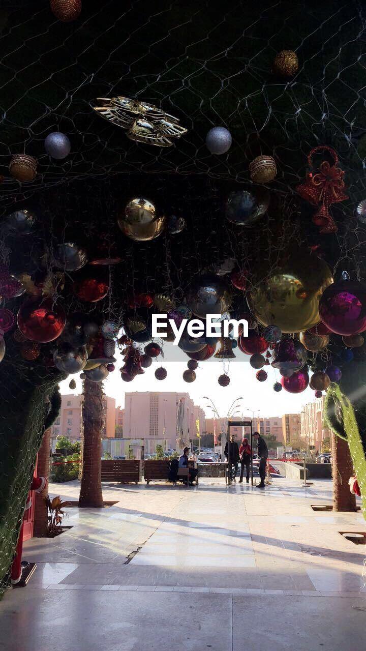 large group of people, hanging, real people, celebration, indoors, illuminated, men, night, christmas decoration, architecture, tree, people
