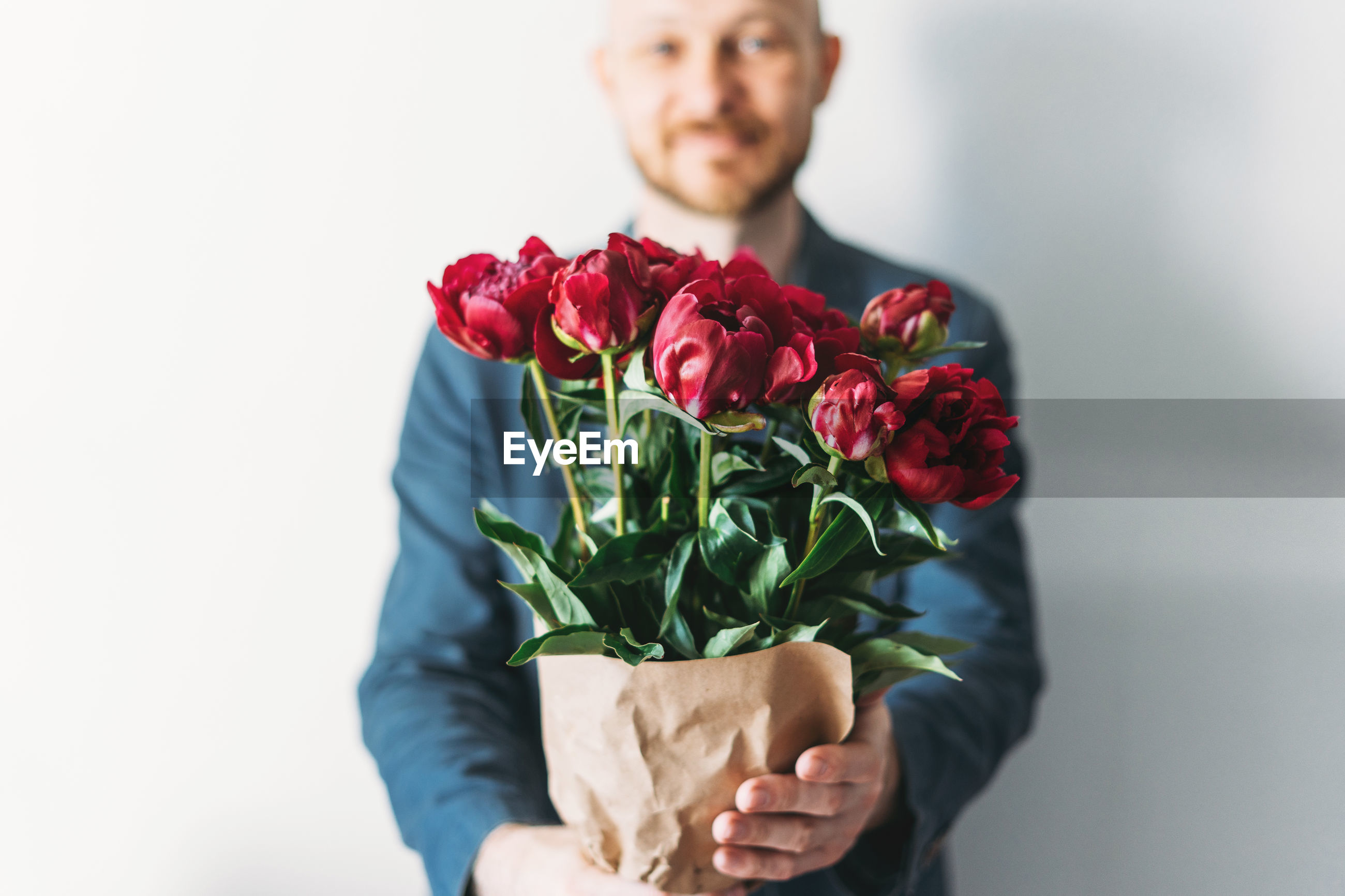 MAN HOLDING ROSE BOUQUET AGAINST WHITE BACKGROUND