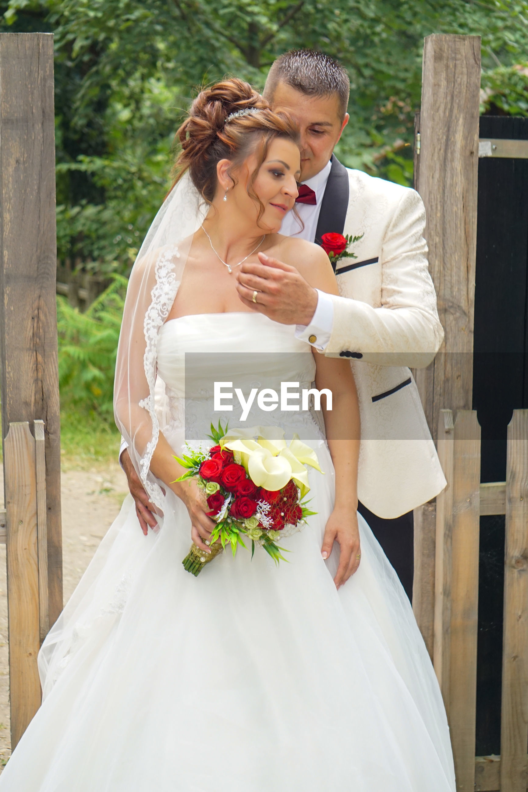 Bride and groom holding flower bouquet while standing against trees