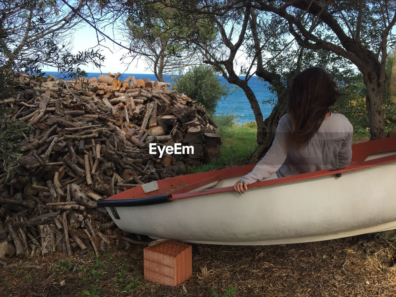Rear view of woman sitting by trees in abandoned boat