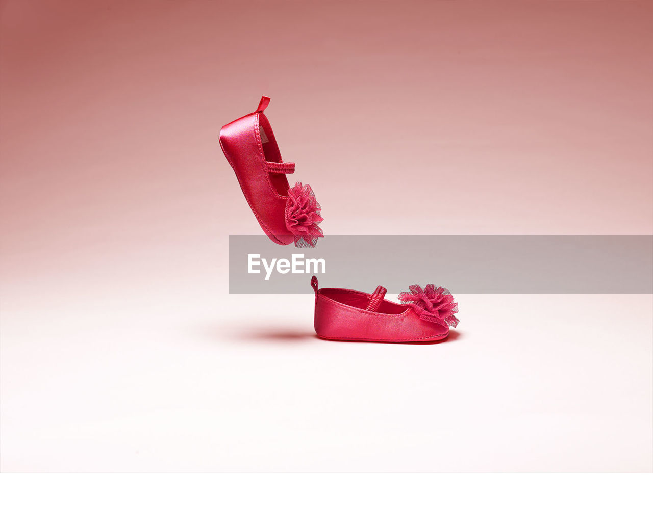 Pink baby booties on white background