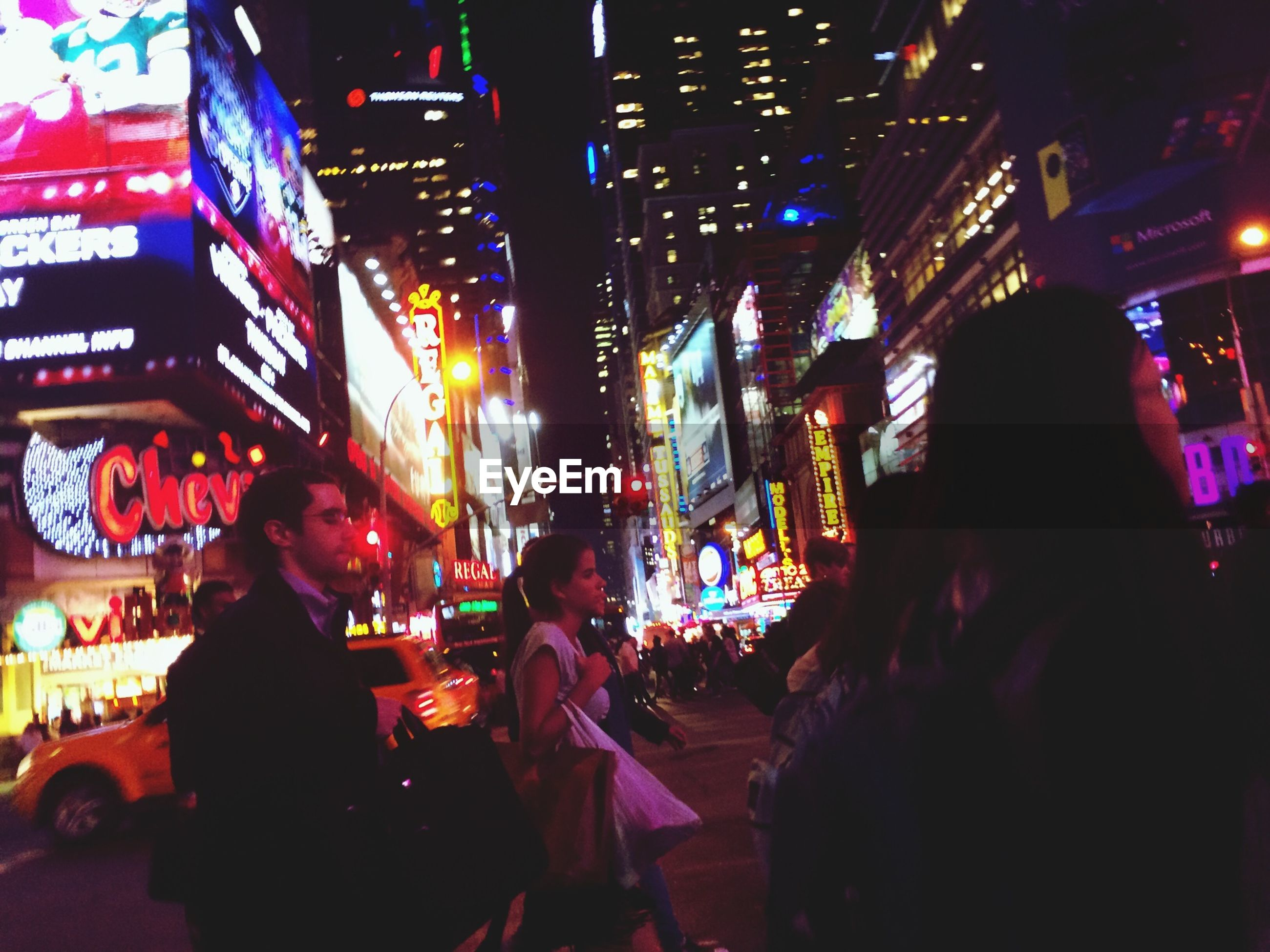 illuminated, night, large group of people, city, architecture, building exterior, built structure, lifestyles, men, person, city life, leisure activity, crowd, lighting equipment, street, arts culture and entertainment, nightlife, light - natural phenomenon, crowded