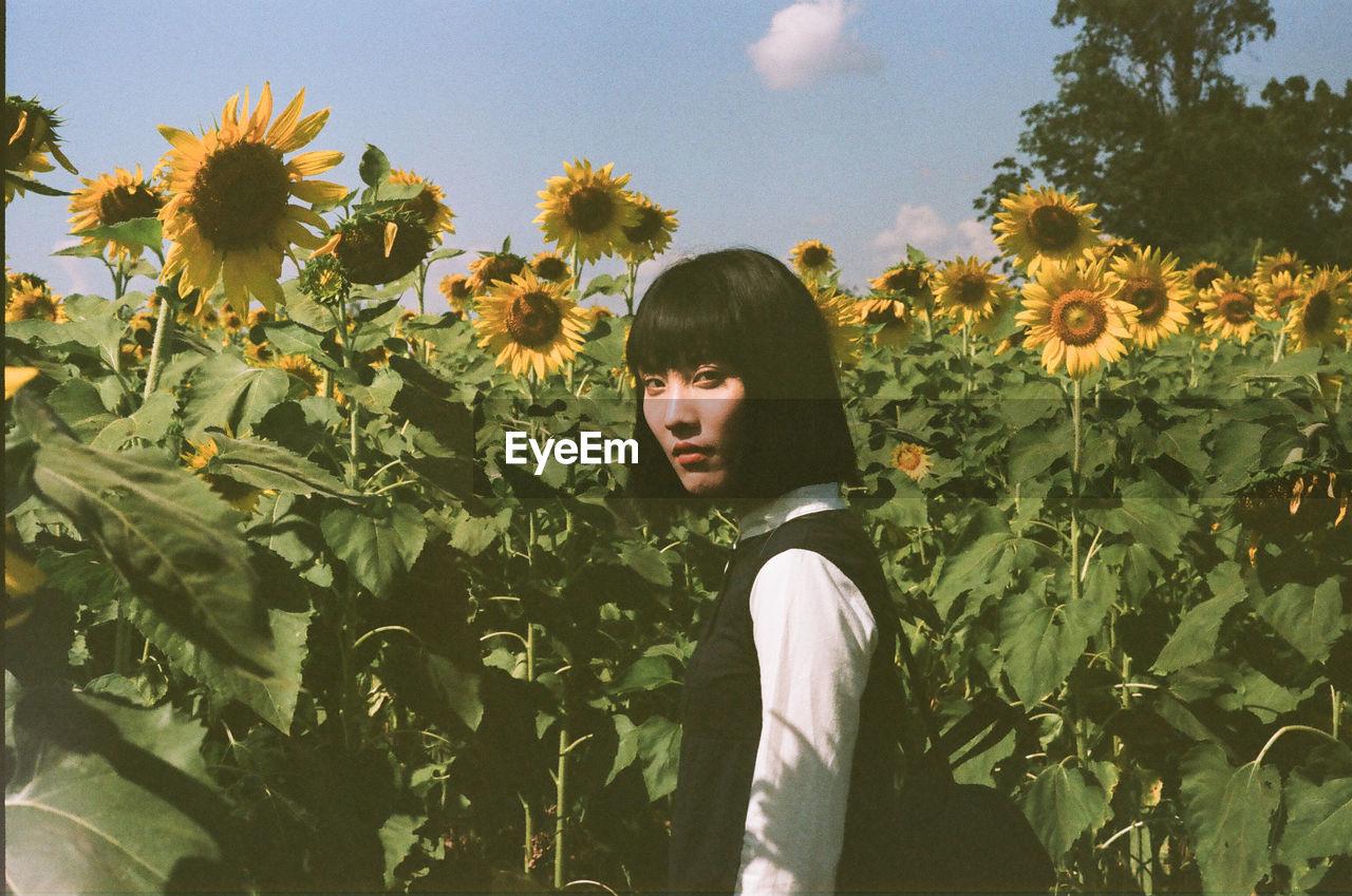 Portrait Of Woman Standing In Sunflower Field