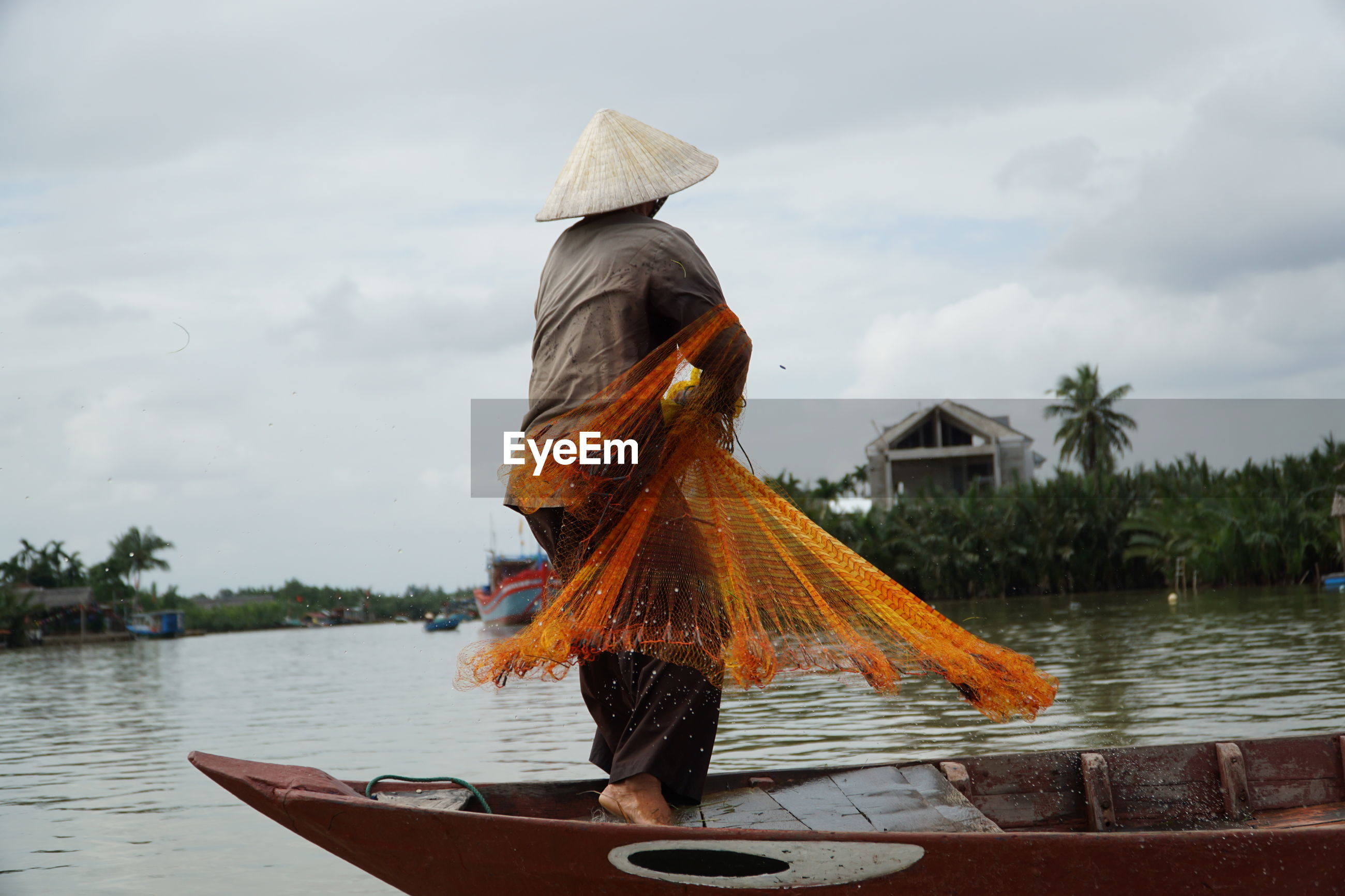 Fisherman throwing net while standing in boat on sea against sky