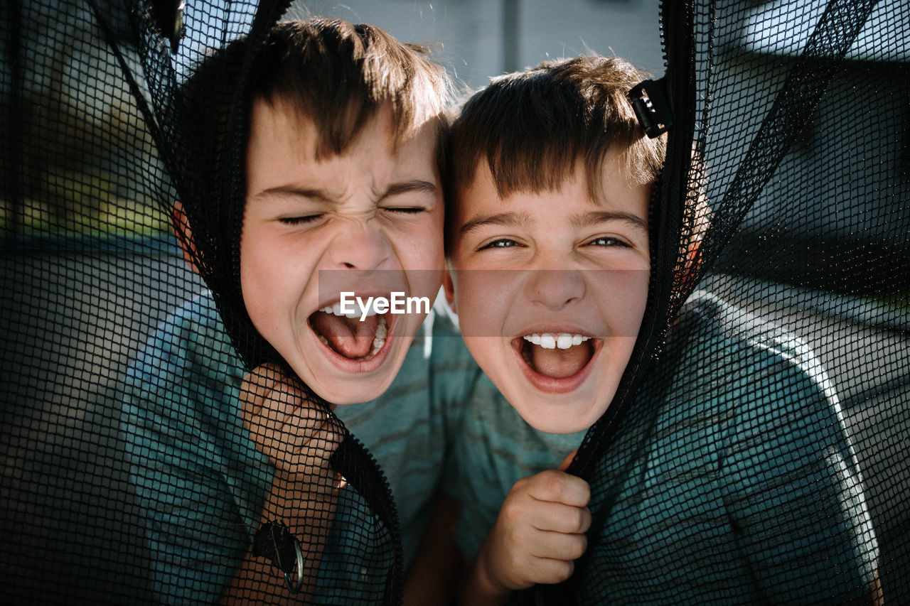 Portrait of laughing boys sitting outdoors