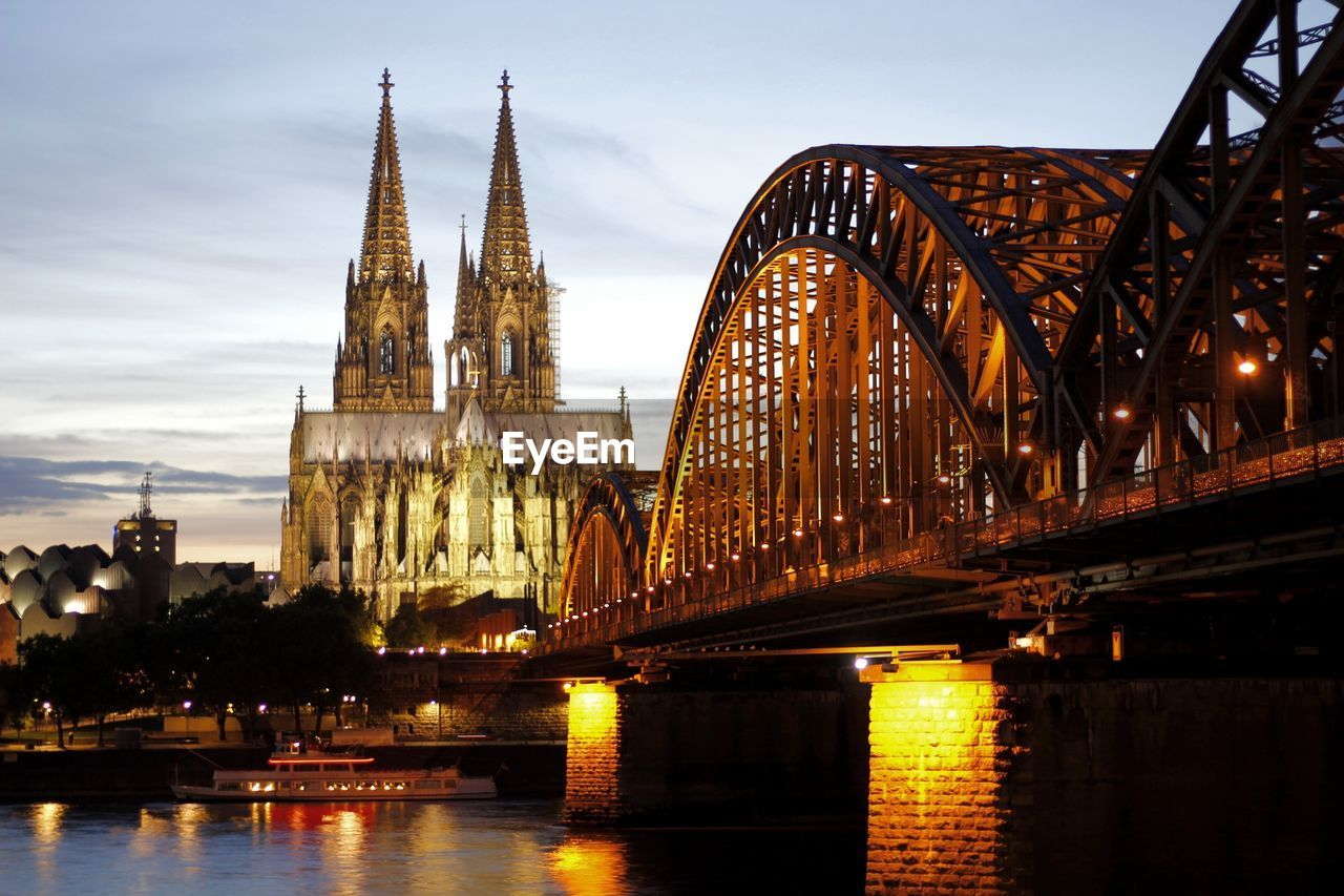 Cologne Cathedral And Illuminated Hohenzollern Bridge Against Sky During Sunset