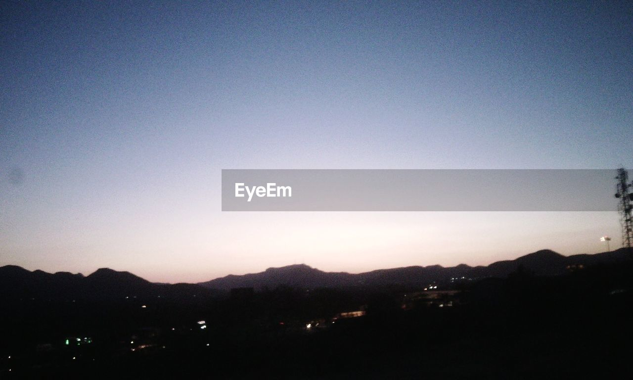 silhouette, night, no people, illuminated, mountain, sunset, clear sky, city, outdoors, sky, nature, architecture