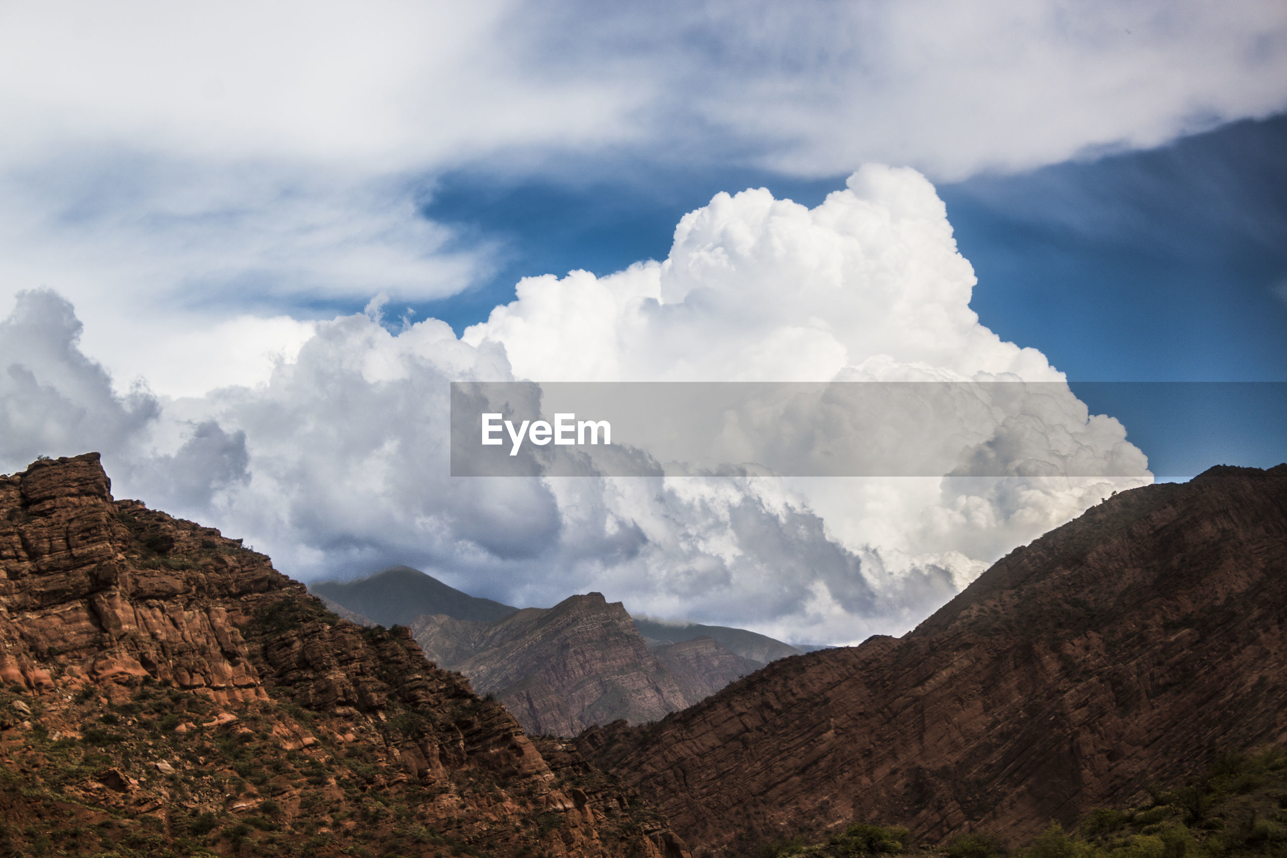 Low angle view of mountains against cloudy sky