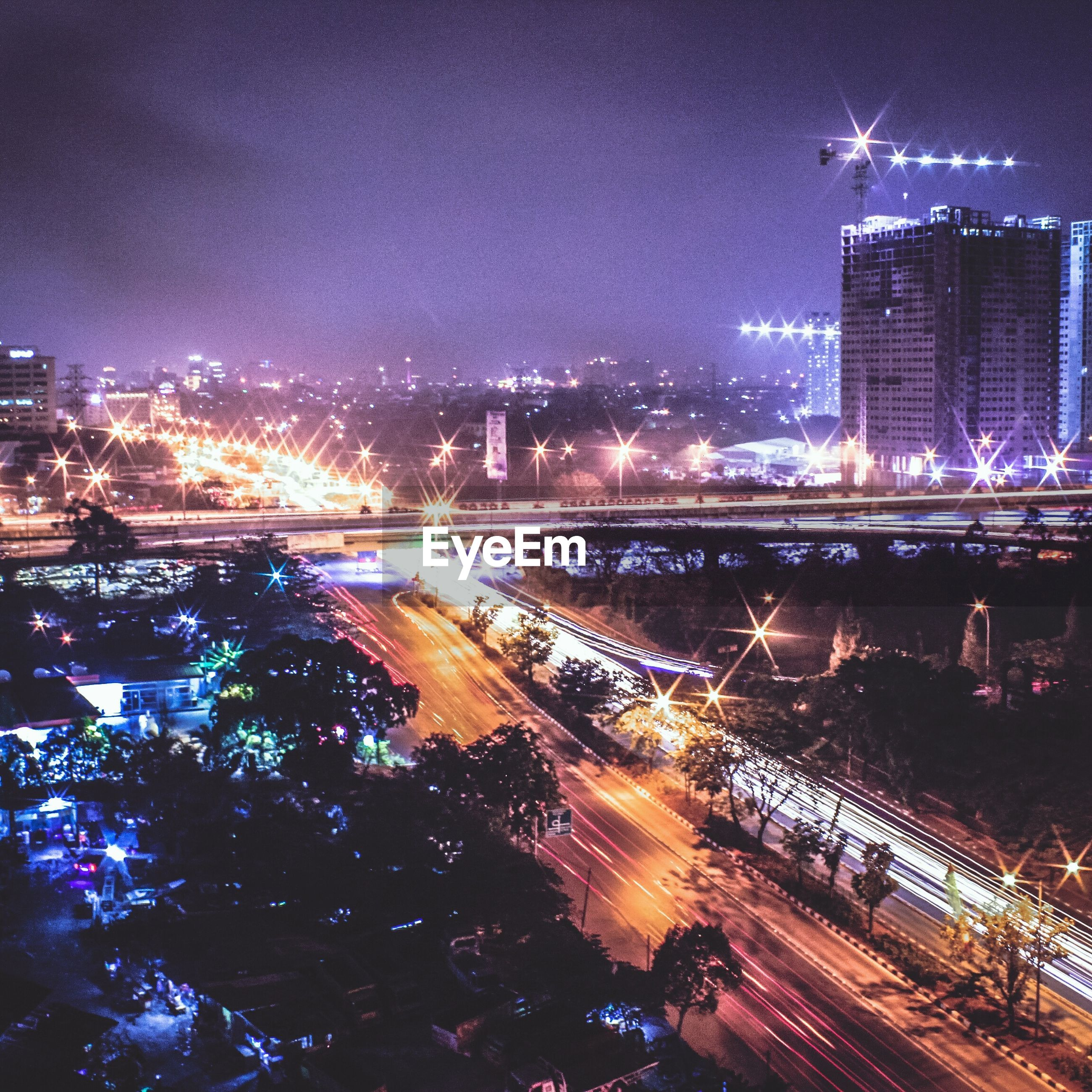 illuminated, night, architecture, city, long exposure, building exterior, motion, light trail, built structure, speed, cityscape, city life, skyscraper, outdoors, blurred motion, no people, sky, transportation, water, road, travel destinations, urban skyline, urban scene, high street