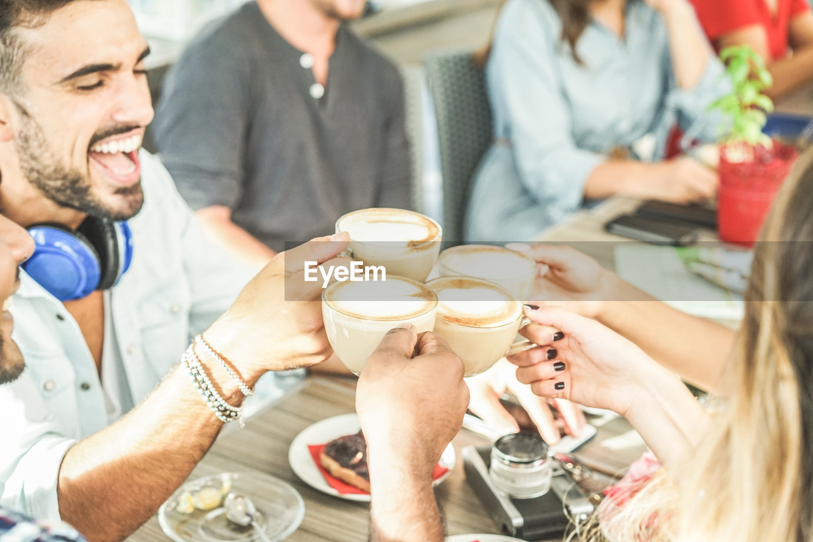 High angle view of happy friends toasting coffee
