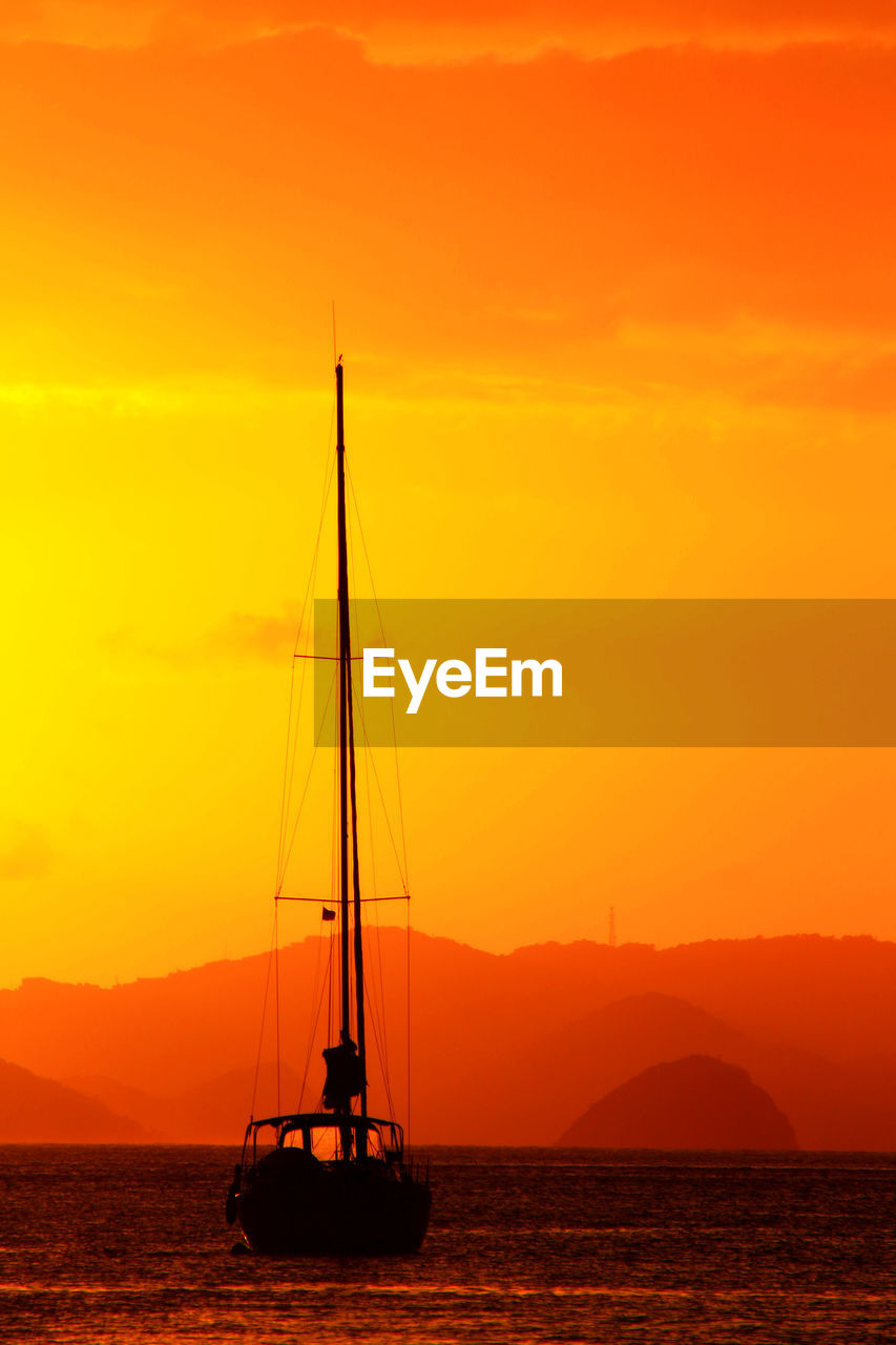 Sailboat Sailing On Sea Against Orange Sky During Sunset