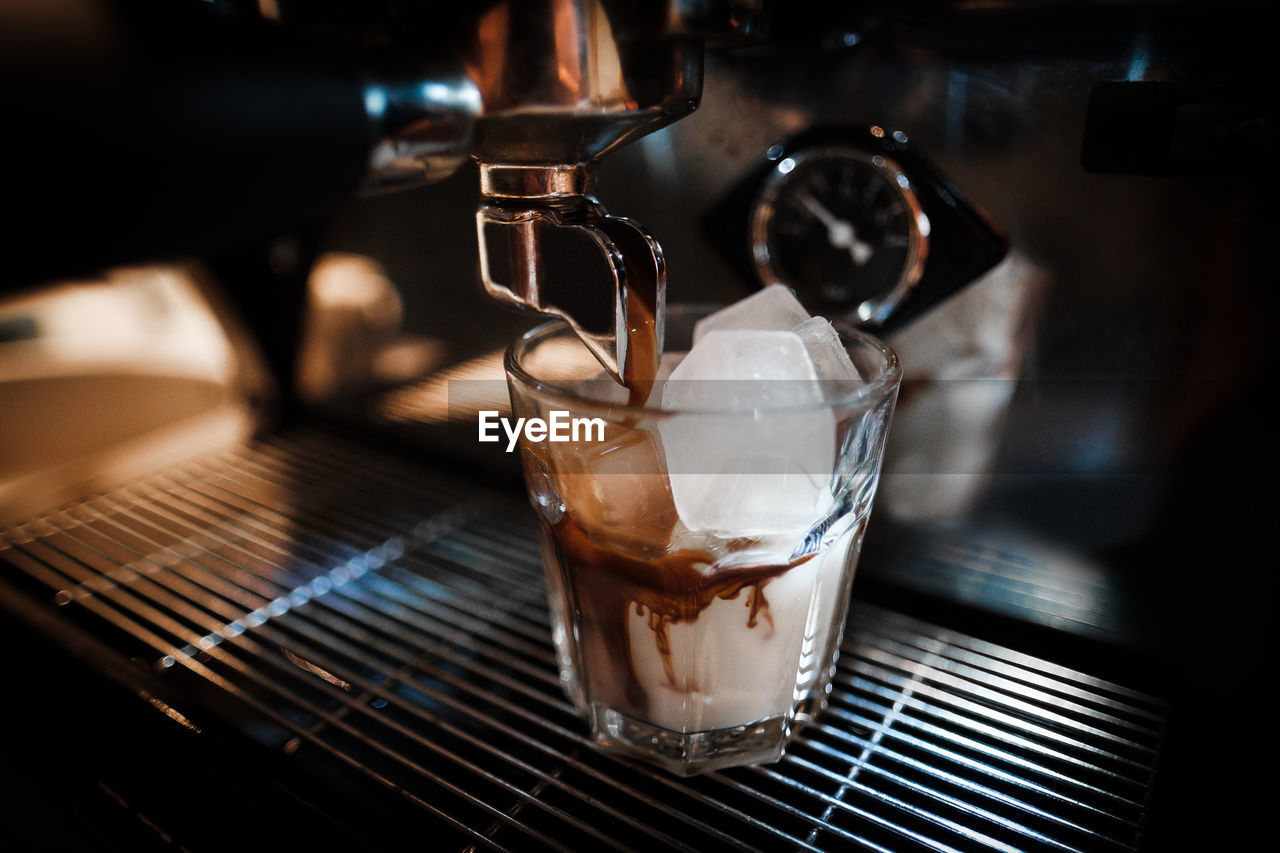 Close-Up Of Coffee Pouring In Drinking Glass At Cafe