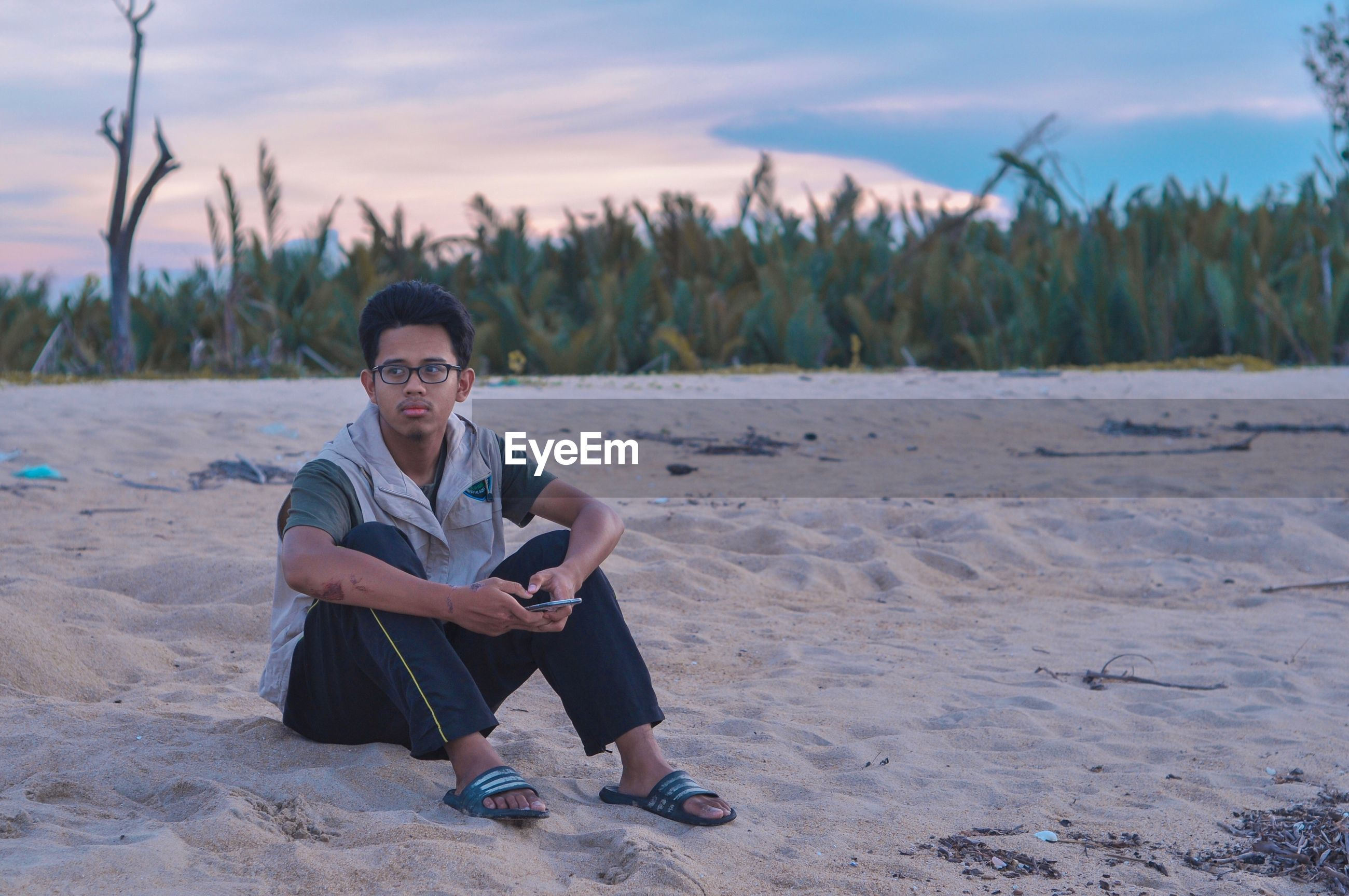 Young man sitting on beach against sky
