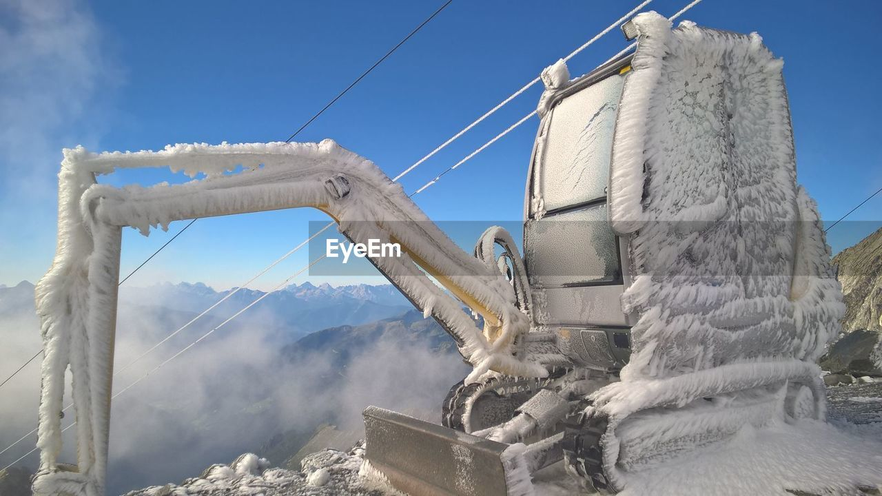 Frozen excavator at construction site against clear blue sky