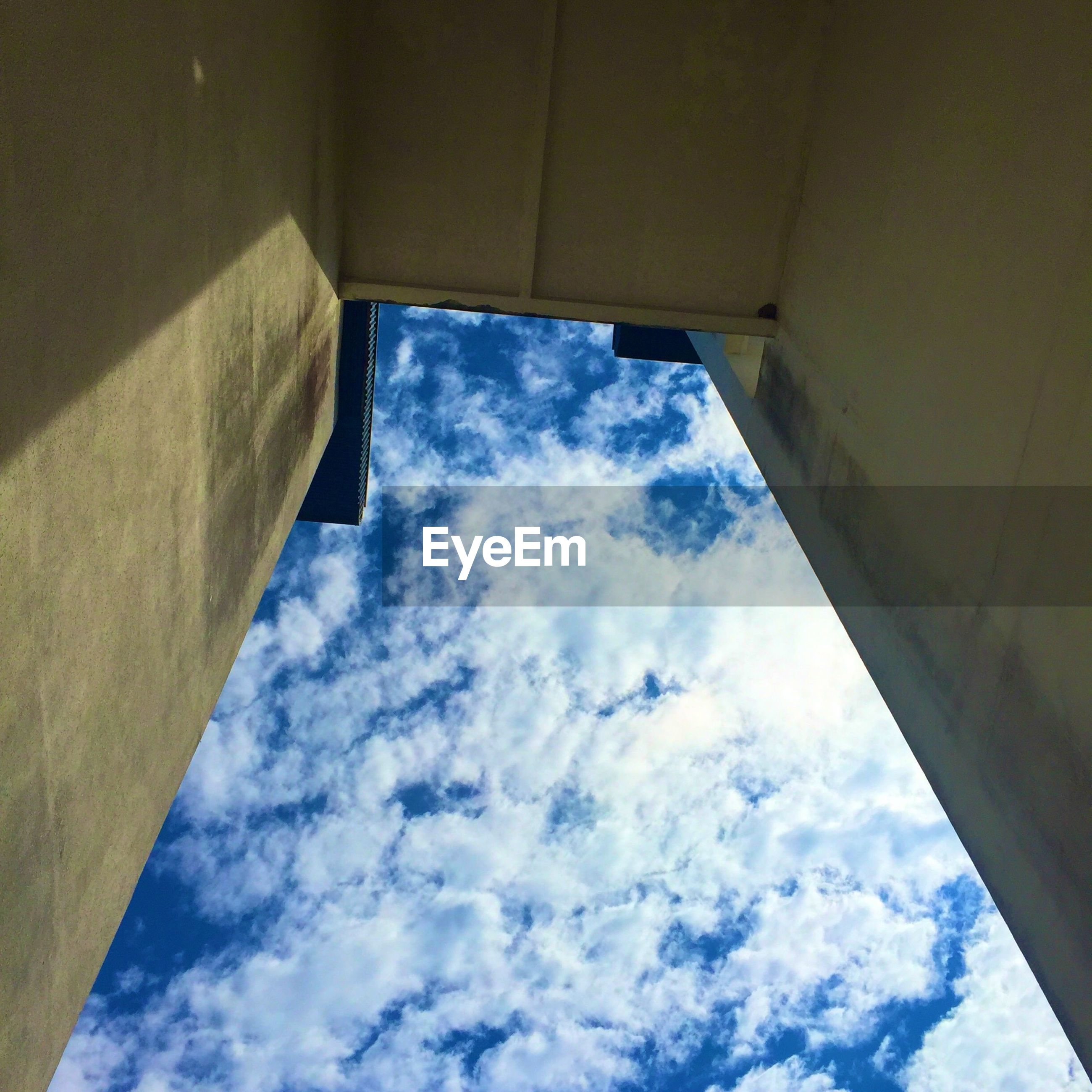 sky, low angle view, architecture, built structure, cloud - sky, window, cloud, building exterior, indoors, cloudy, day, building, directly below, no people, sunlight, blue, house, wall - building feature, glass - material