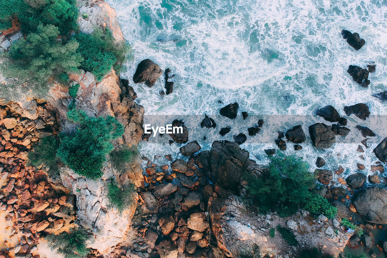 rock, solid, rock - object, sea, water, motion, high angle view, nature, beauty in nature, land, day, no people, beach, sport, wave, outdoors, aquatic sport, rock formation, power in nature, breaking, eroded