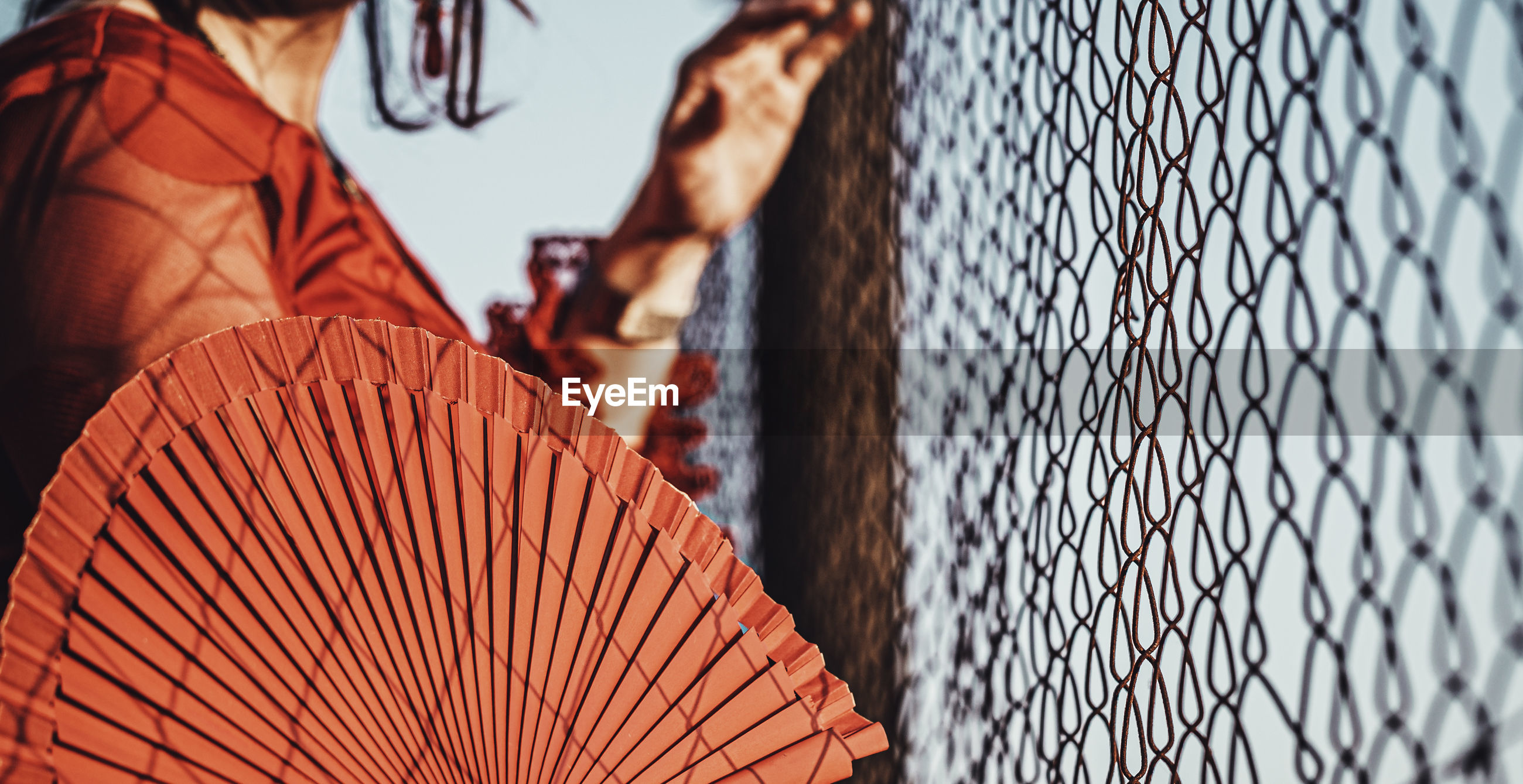 Midsection of woman holding hand fan by chainlink fence