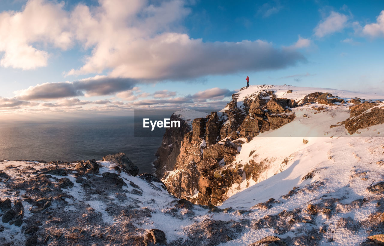 sky, cloud - sky, beauty in nature, scenics - nature, cold temperature, winter, tranquil scene, nature, rock, tranquility, rock - object, snow, solid, non-urban scene, mountain, day, leisure activity, rock formation, water, outdoors, snowcapped mountain