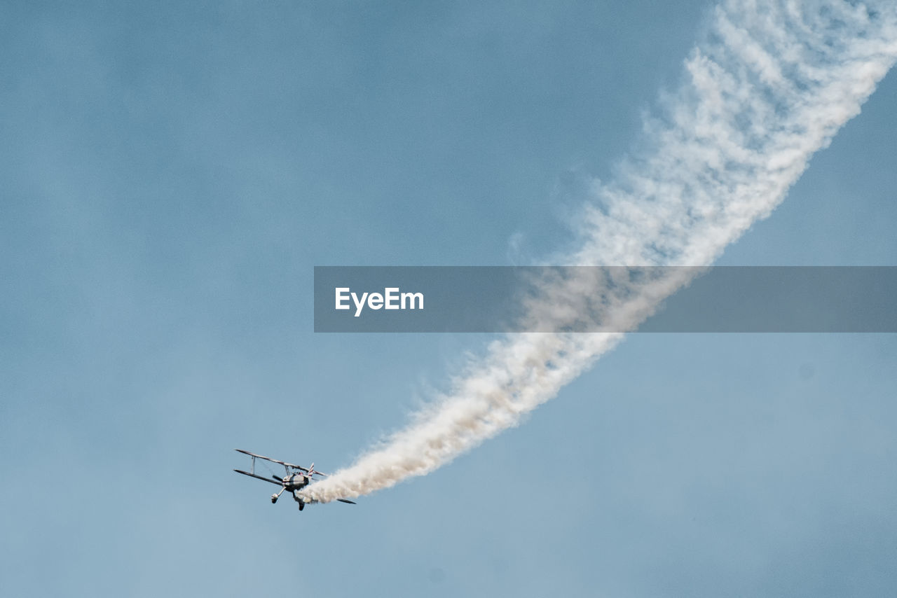 Low Angle View Of Military Airplane Performing Airshow Against Blue Sky
