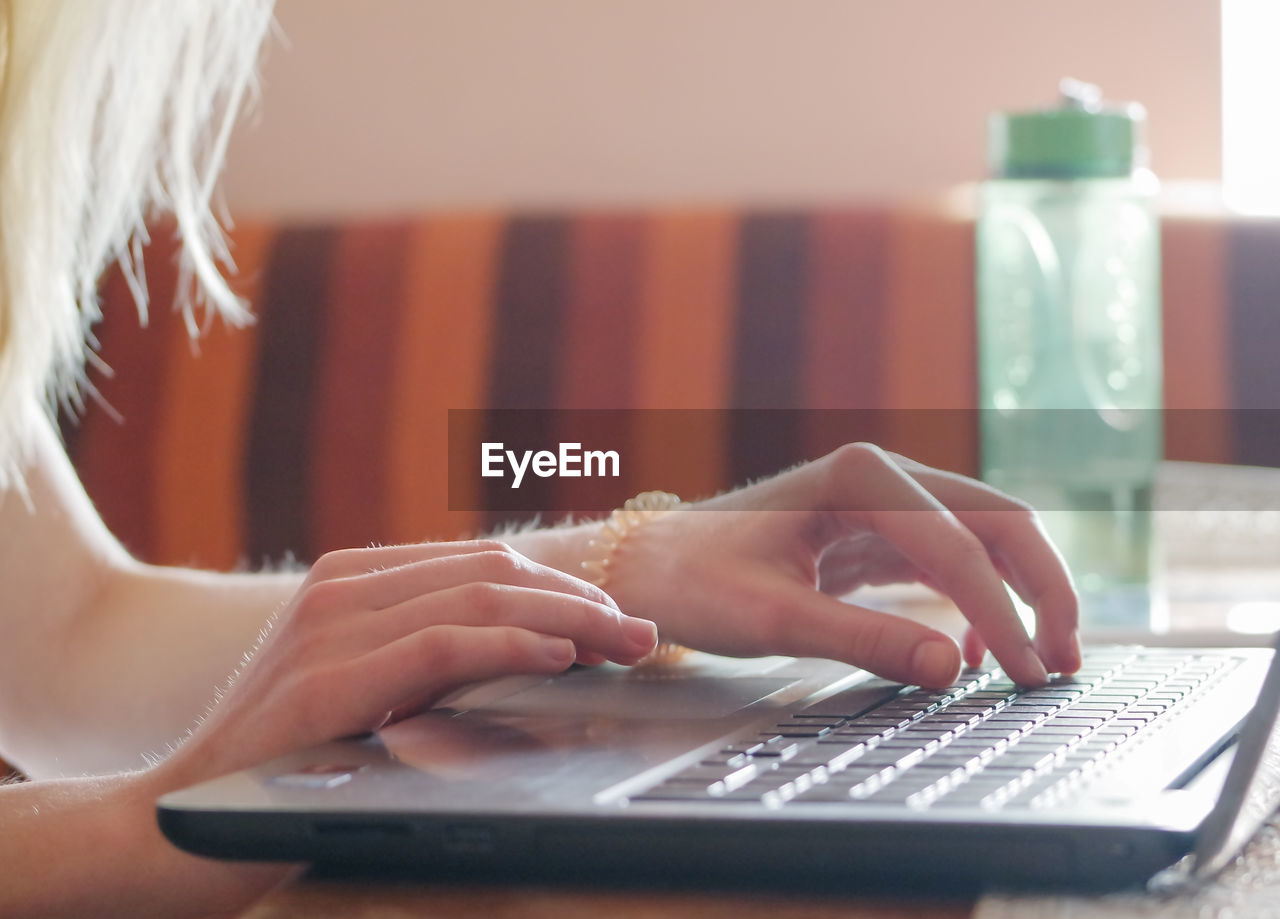 Cropped Hands Of Woman Using Laptop At Home
