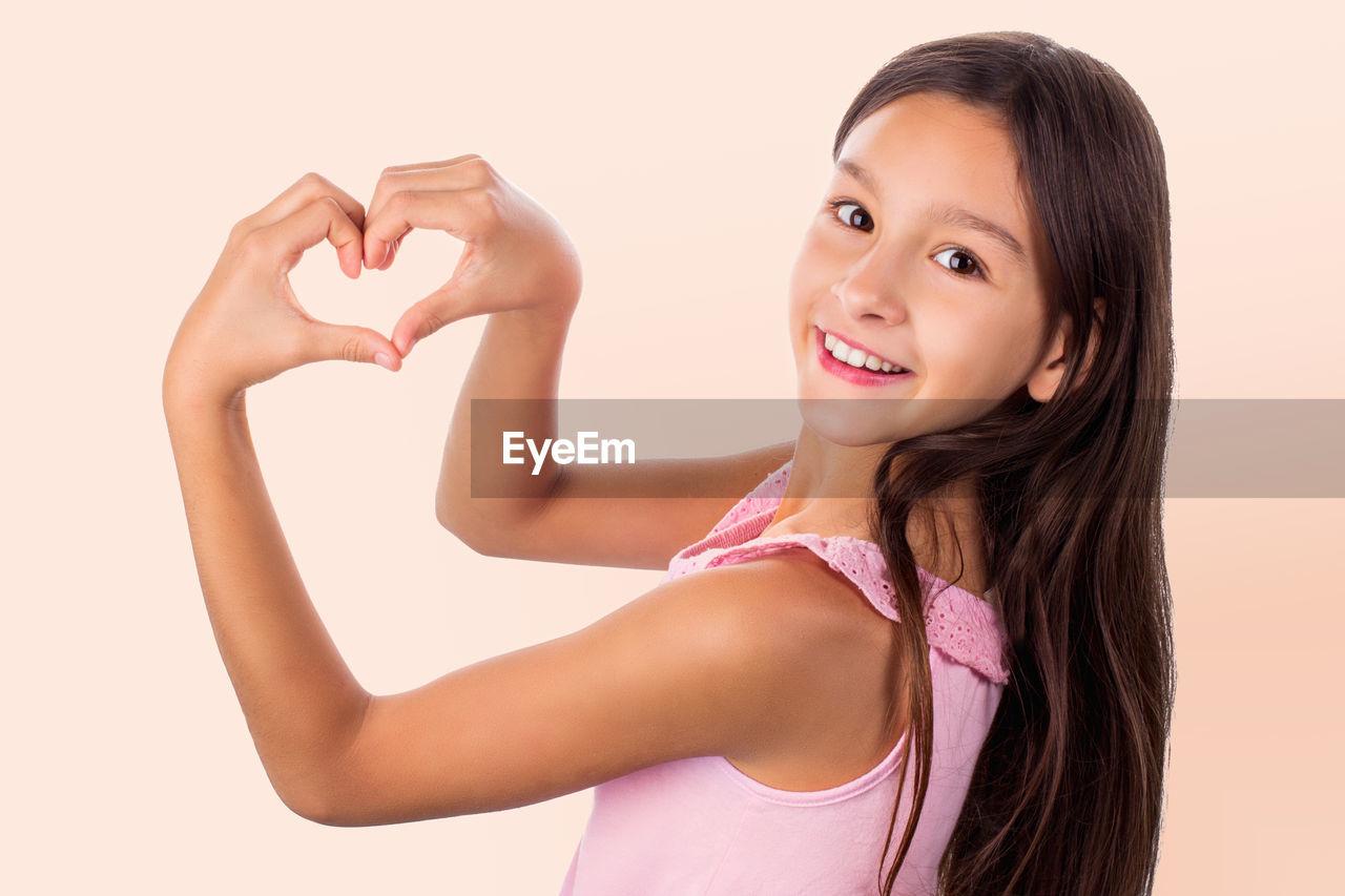Portrait of smiling girl making heart shape against beige background