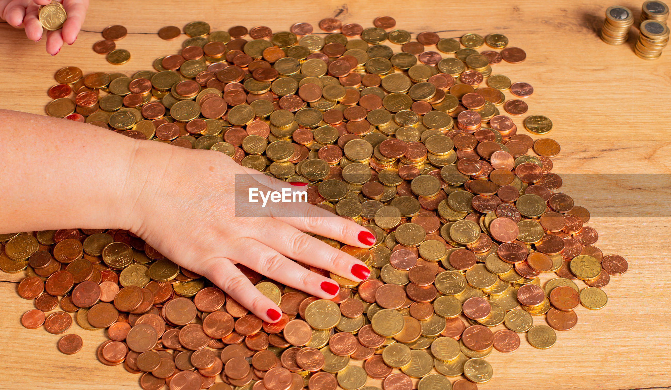 High angle view of woman hand counting coins on table