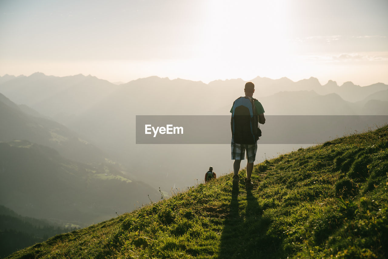Rear View Of Male Hiker Looking At Mountains Against Sky During Sunset